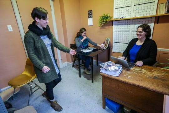 Geez magazine's associate editor Kateri Boucher, walks over to editor Lydia Wylie-Kellermann's desk as art director Lucia Wylie-Eggert, in back, works from her desk in their office at St. Peter's Episcopal Church's historic Peace and Justice Hive in the Corktown neighborhood of Detroit, photographed on Thursday, Feb. 7, 2019.
