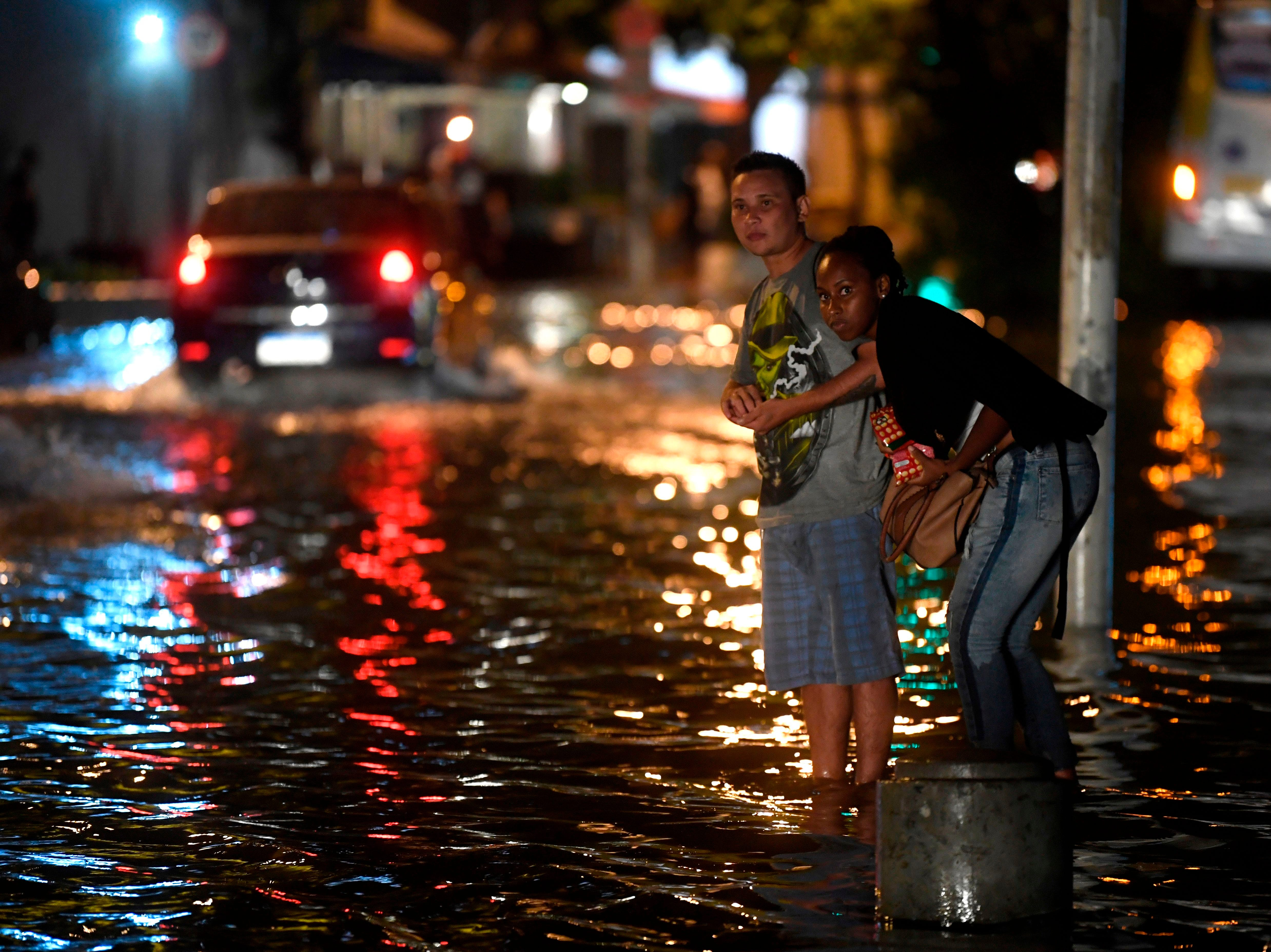 People watch for a bus at the Voluntarios da Patria street station in the Botafogo neighborhood after a strong rain flooded multiple areas of Rio de Janeiro, Brazil on Feb. 7, 2019.