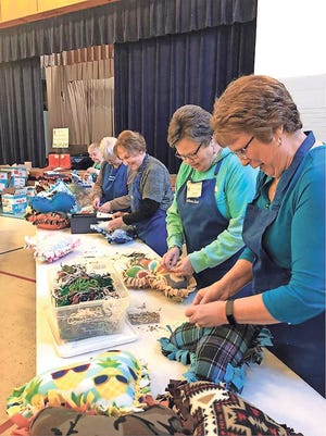 Members of the Immanuel Lutheran Prayer Blanket Ministry attach hangtags to handmade fleece pillows to be donated to 1,400 foster children on Valentine's Day.