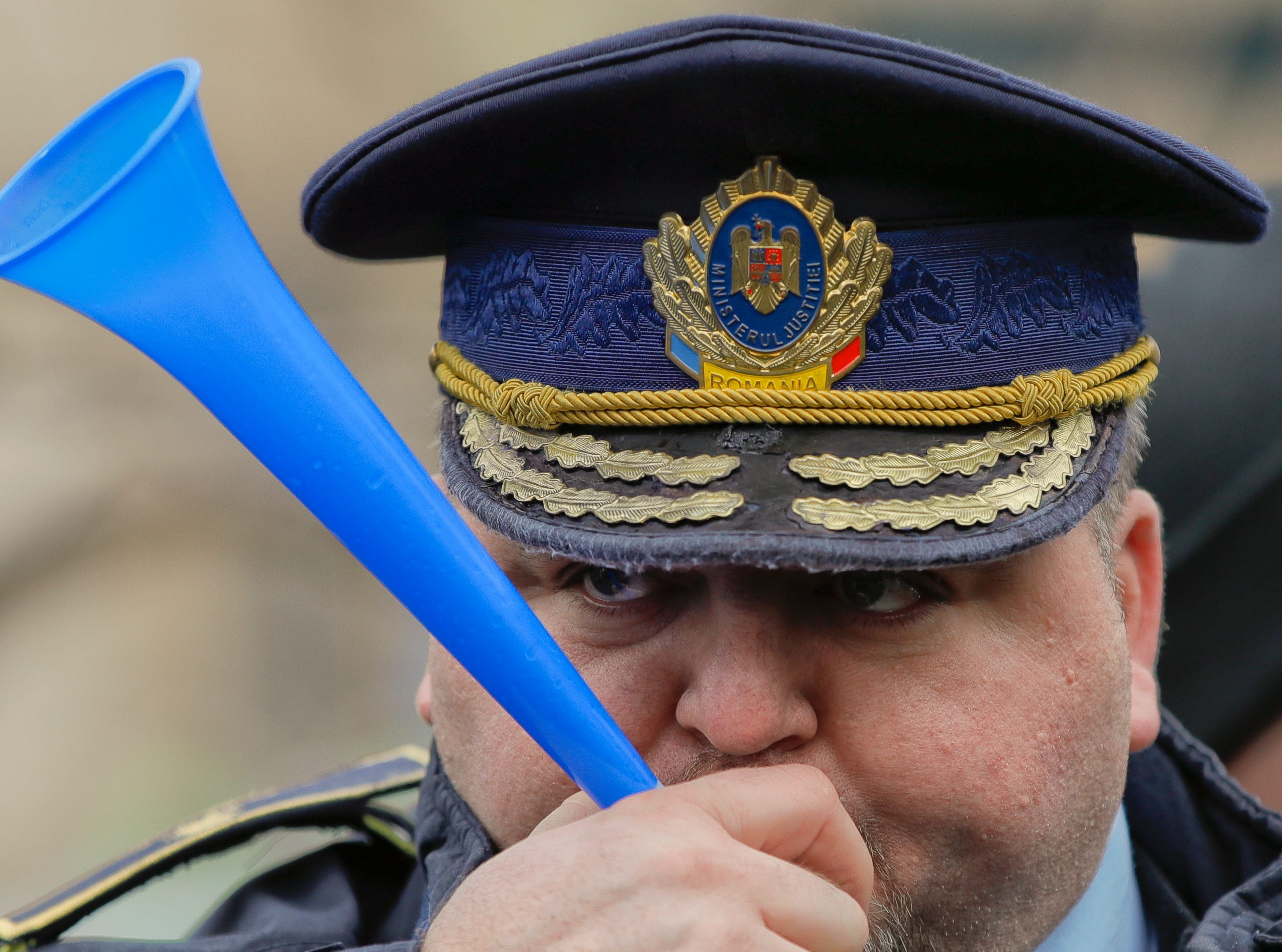 A penitentiary system security officer sounds a horn during a protest outside the Interior Ministry headquarters in Bucharest, Romania, Thursday, Feb. 7, 2019. Police, security officers of the penitentiary system and retired military personnel joined a protest asking for better working conditions, safety equipment, salaries and pensions.