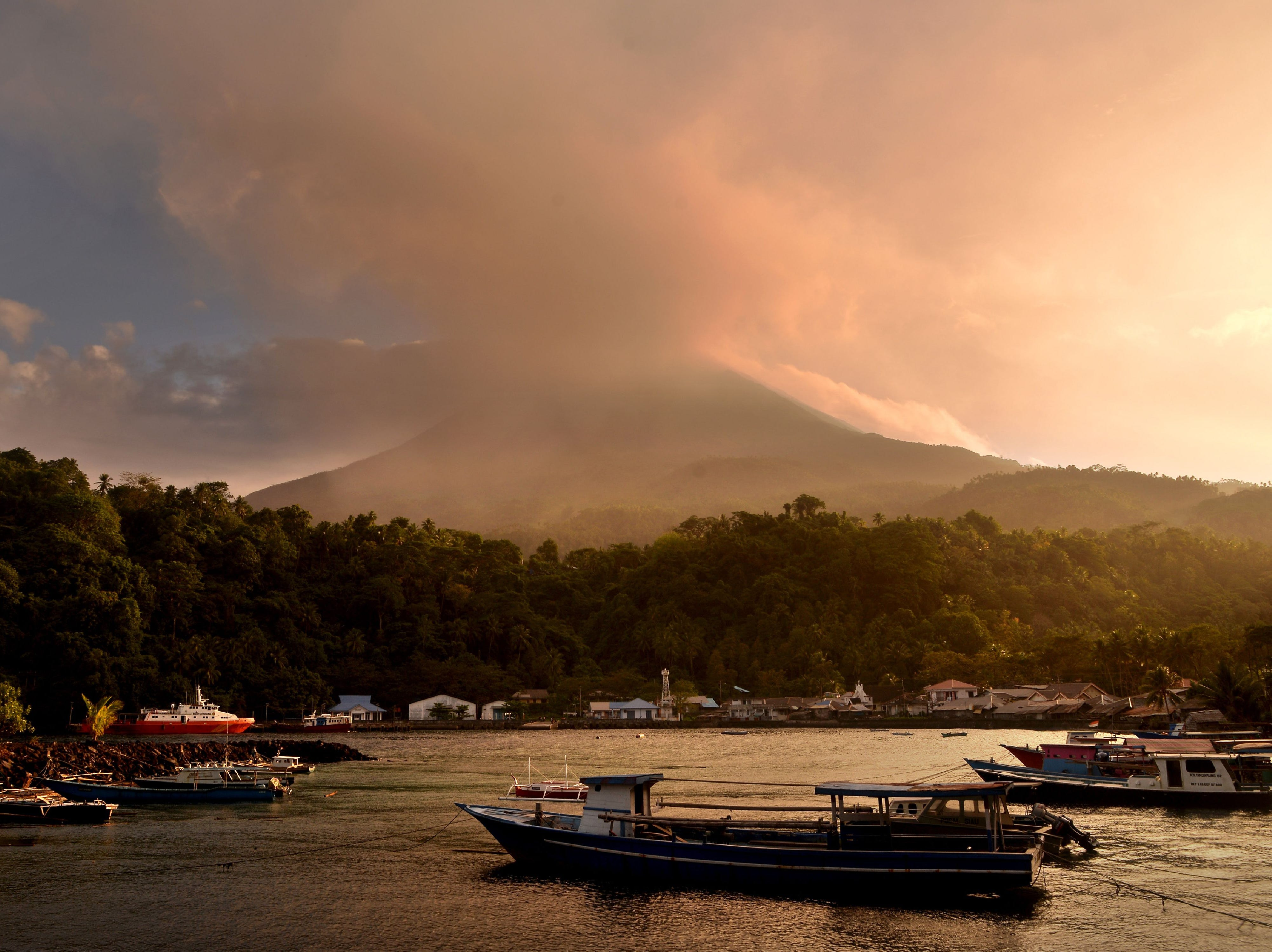 This picture taken at Pehe port on Siau island, Indonesia's North Sulawesi province, shows the Karangetang volcano spewing smoke on Feb. 7, 2019. The volcano has been active and forced dozens of people to evacuate on Feb. 4.