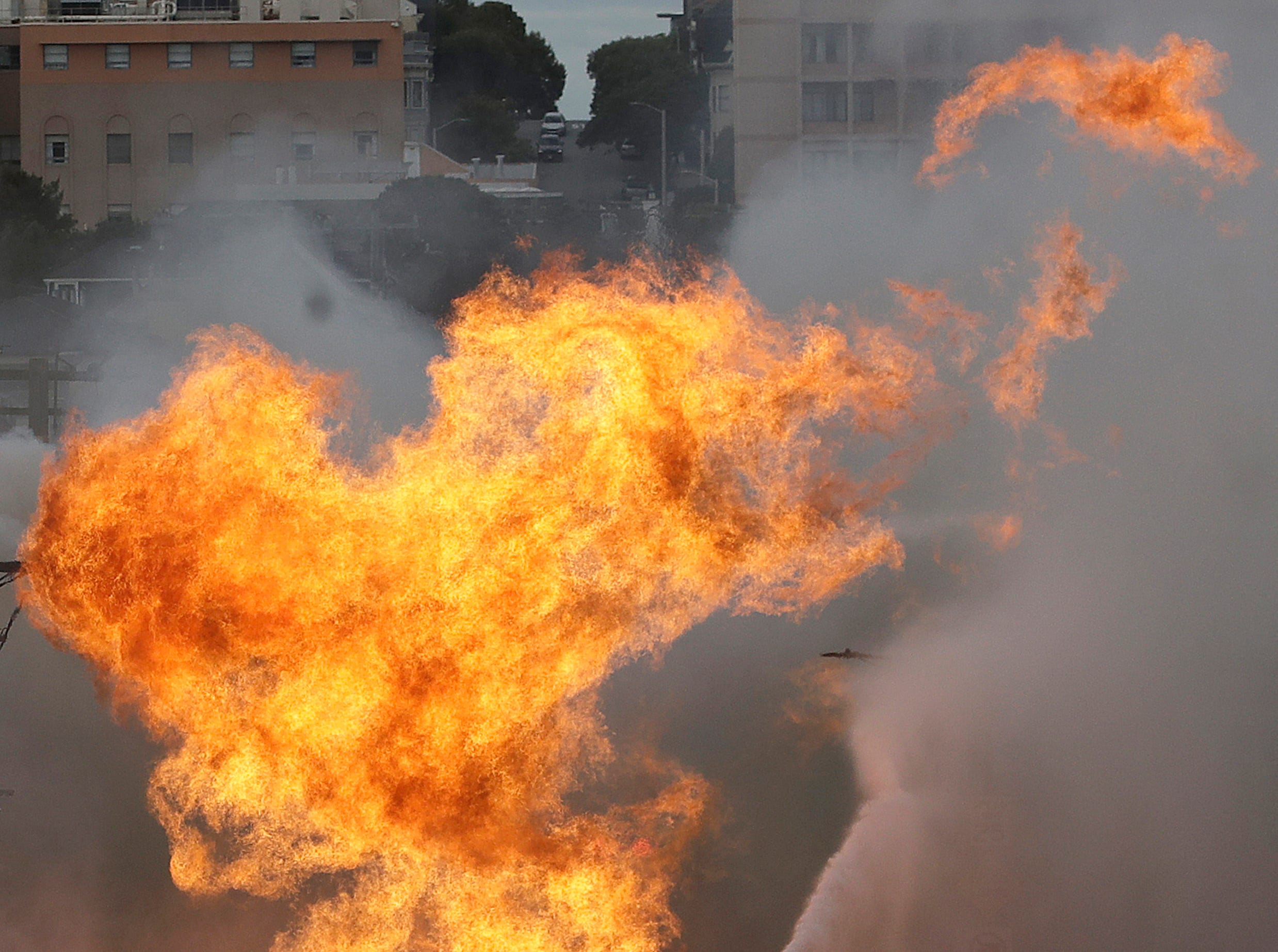 San Francisco firefighters battle a fire on Geary Boulevard in San Francisco, Wednesday, Feb. 6, 2019. A gas explosion in a San Francisco neighborhood shot flames high into the air Wednesday and was burning several buildings as utility crews scrambled to shut off the flow of gas. Construction workers cut a natural gas line, San Francisco Fire Chief Joanne Hayes-White said.