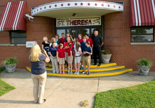 The 8th grade class at St. Theresa Catholic School in Evansville, Ind., lines up in front of the school for a class picture on the first day of school on Tuesday, July 29, 2014. School librarian Peggy Epley (foreground) was taking the picture that their teacher, Ashley Burns (standling beside the students at left) said would be used in the yearbook and would allow them to see how they changed by the end of the school year. The school, built in 1948, closed in 2015 and is going to be razed.