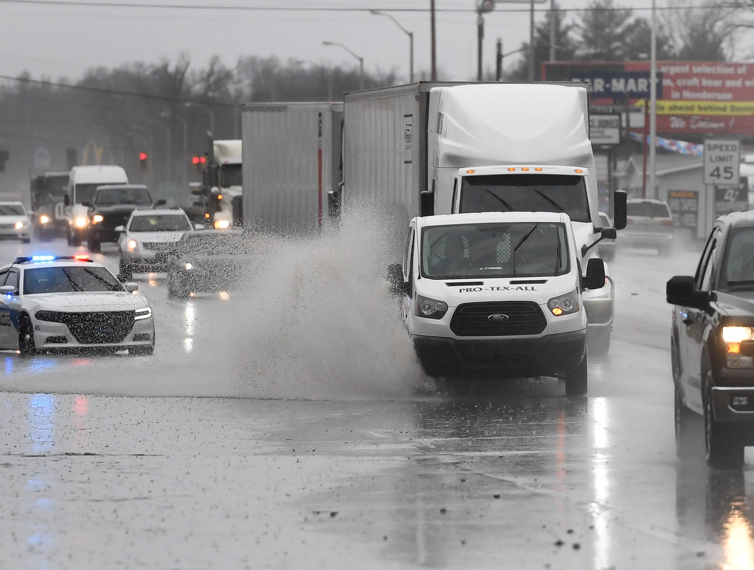 Police divert traffic away from a flooded lane on U.S. 41 North near Audubon State Park following a mid-day downpour Thursday, February 7, 2019.