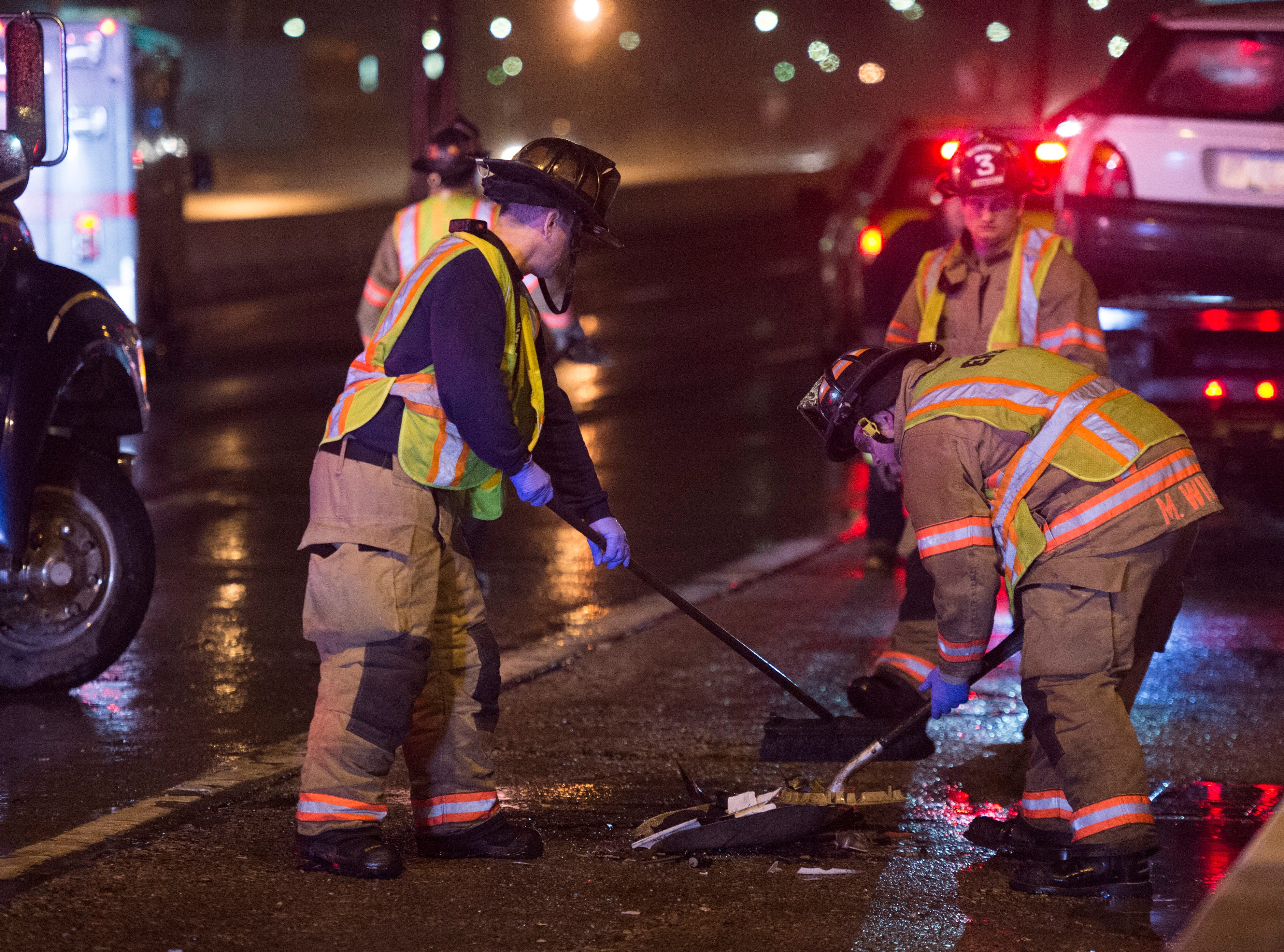 Evansville firefighters sweep up debris on the Lloyd Expressway after two vehicles collided Wednesday, Feb. 6, 2019.