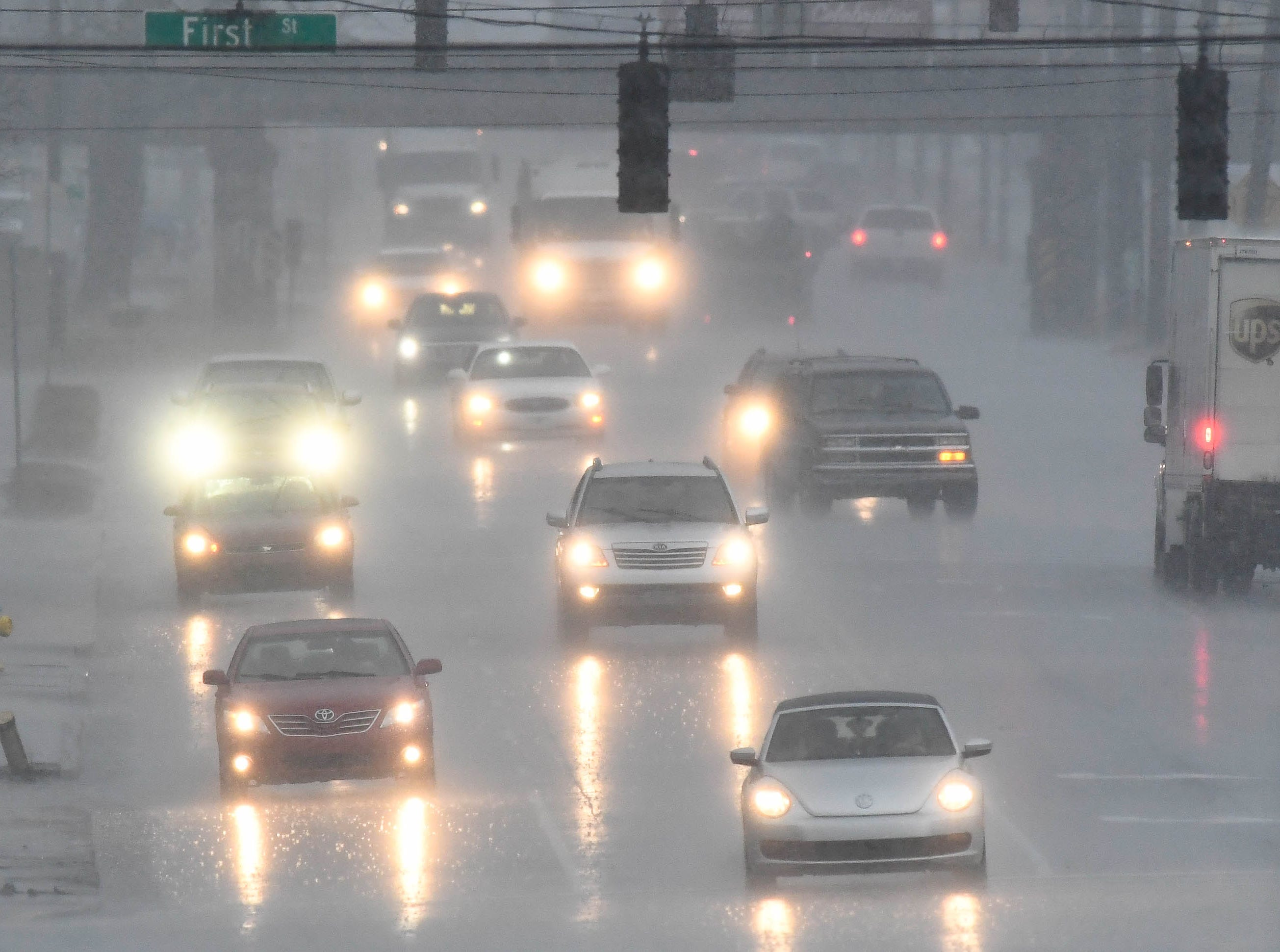 Traffic on North Green Street, in Henderson, during a mid-day downpour as a major storm system makes its way across the area Thursday, February 7, 2019.