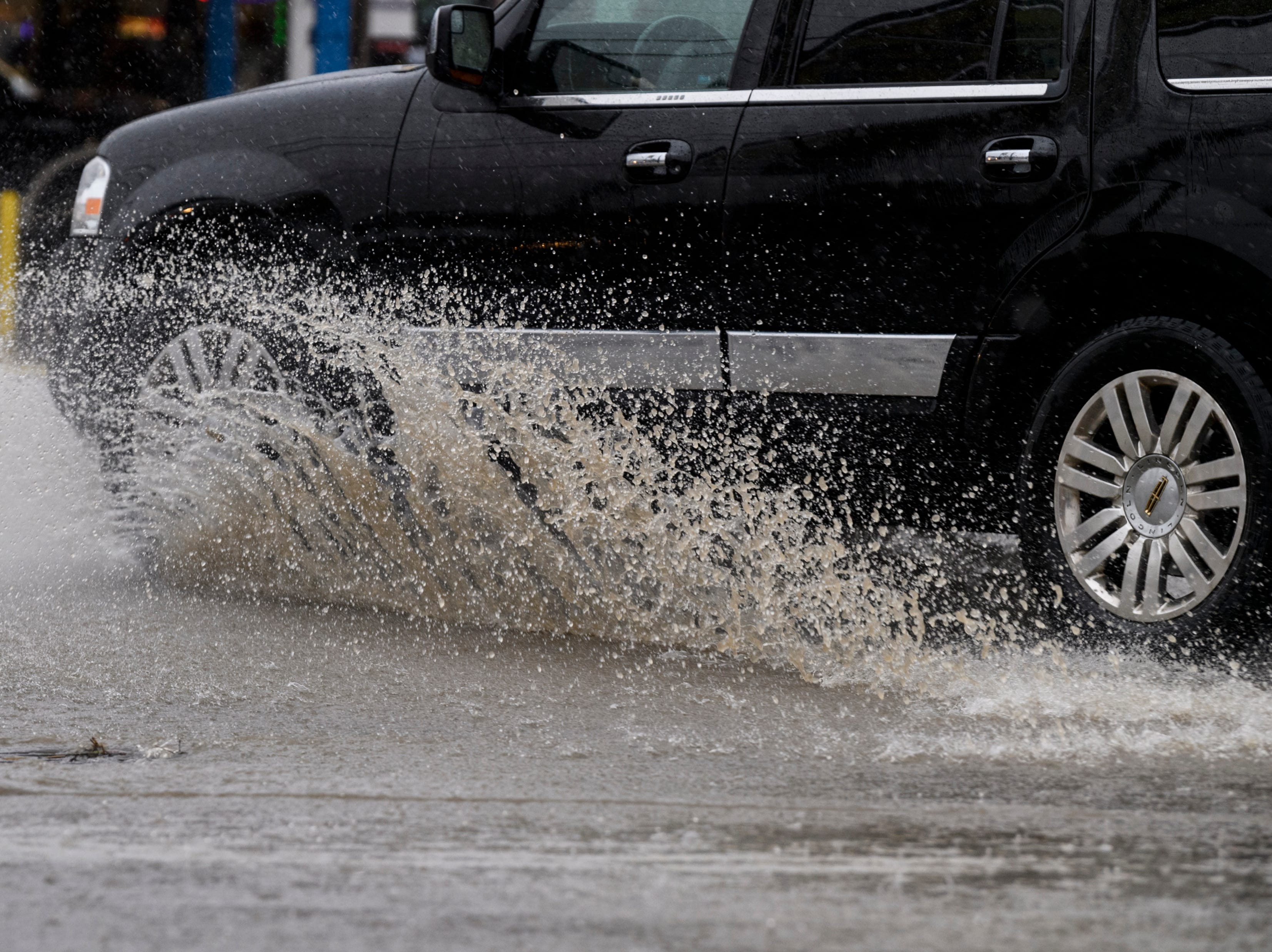 A vehicle drives through standing water at the intersection of North Tekoppel Avenue and Upper Mount Vernon Road on Evansville's west side as heavy rain hit the area, Thursday morning, Feb. 7, 2019.