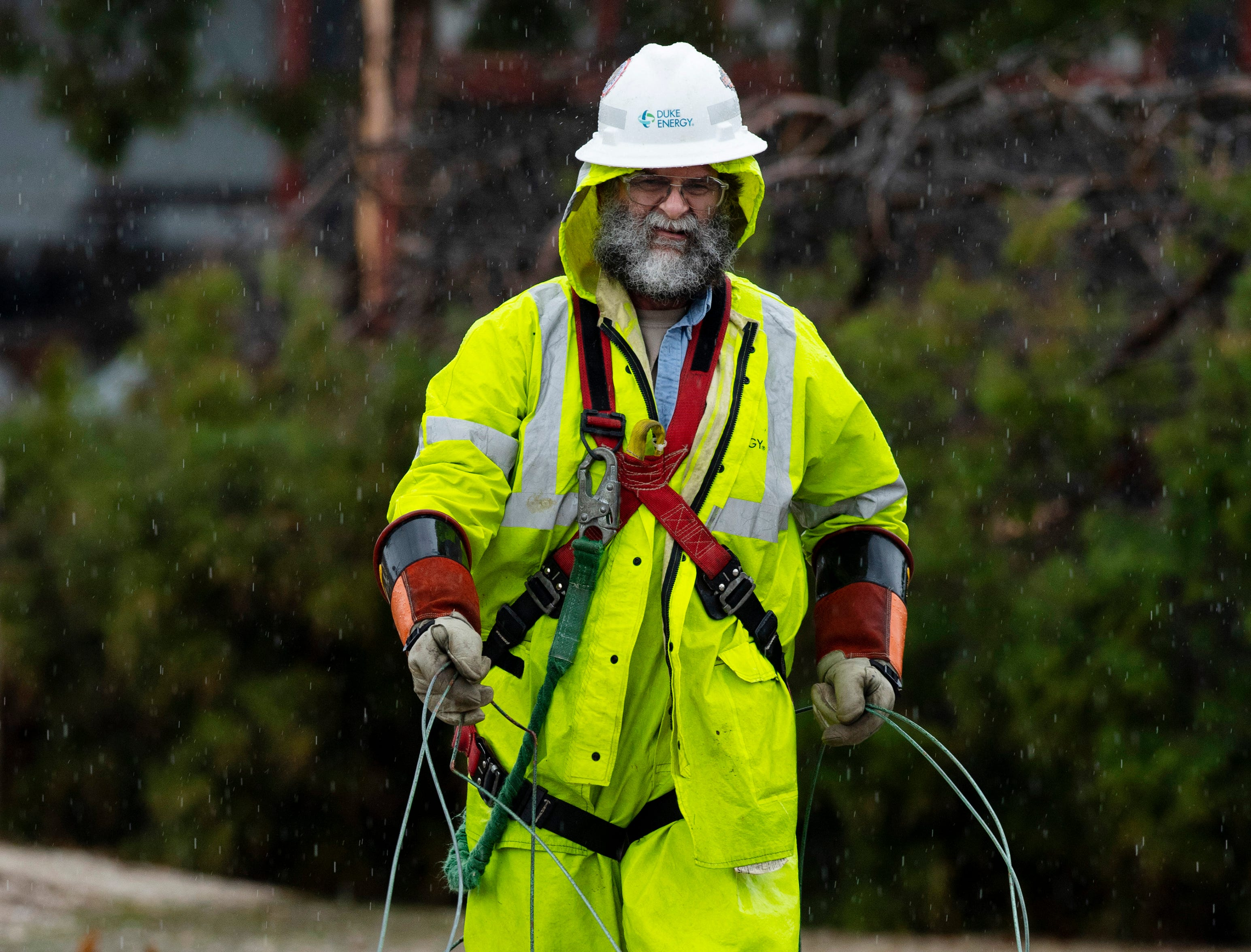 A Duke Energy lineman, who preferred to go nameless, collects dead power lines in Oakland City, Ind., after a storm blew threw the Gibson County town leaving downed trees and some homes missing roofs Thursday morning.
