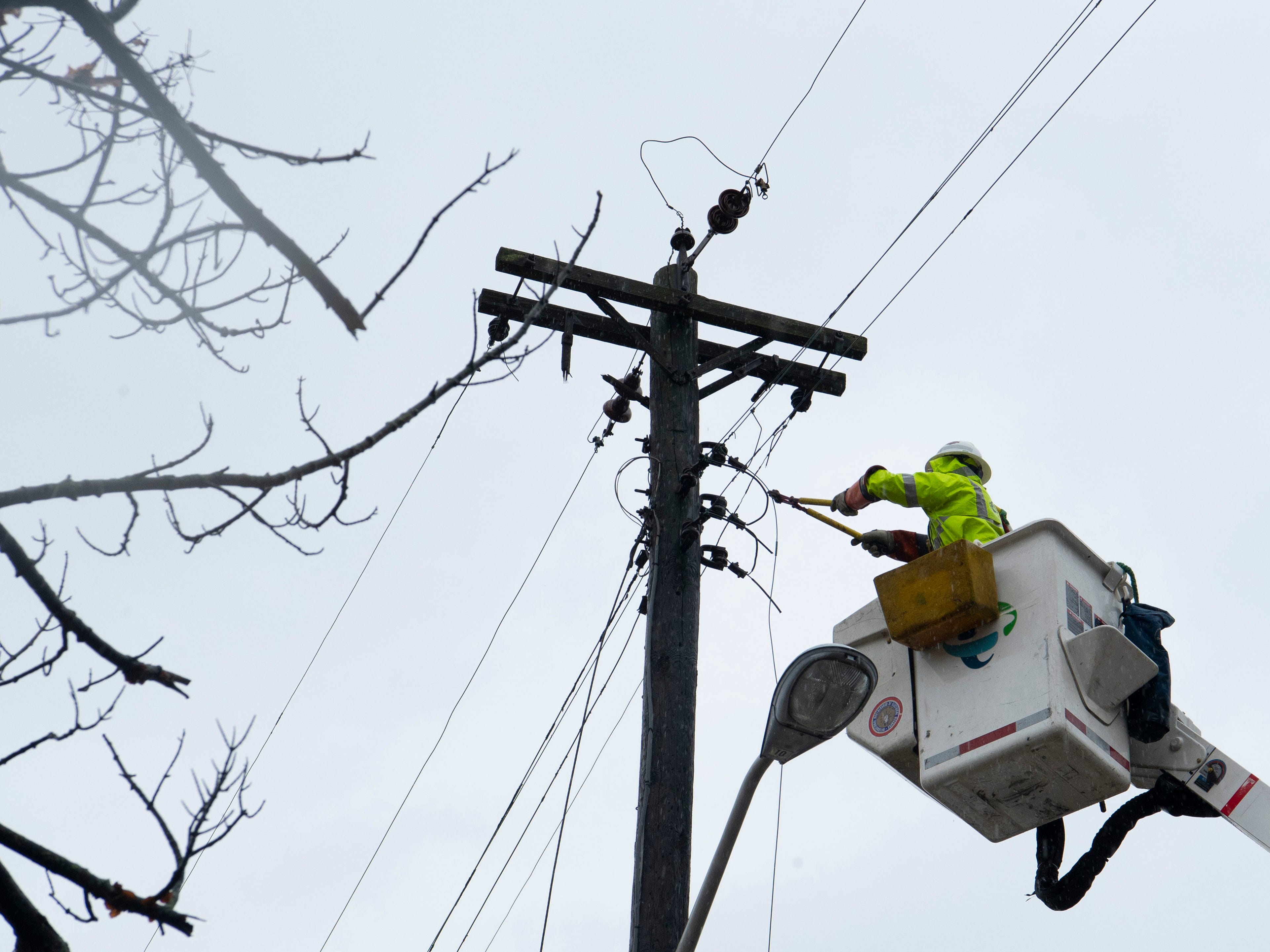 A Duke Energy lineman who preferred to go nameless, cuts dead power lines in Oakland City, Ind., after a storm blew threw the Gibson County town leaving downed trees and some homes missing roofs Thursday morning.