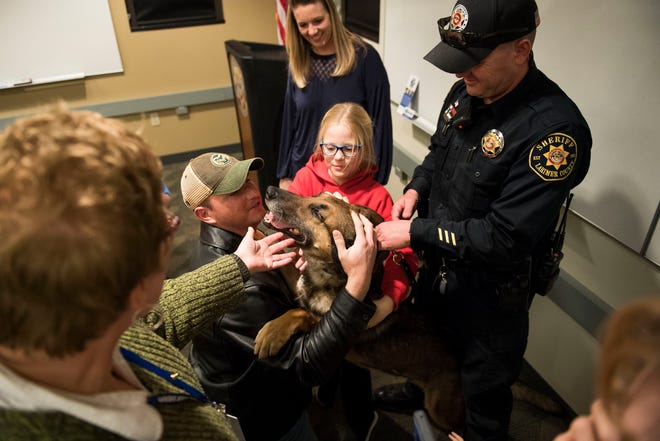Larimer County Sherriff's Department retiring K9 deputy Ryker gets petted by Sherriff's Department K9 agitator Steve Niswender, left, and Alyssa Hulme, 10, while being held by his handler deputy Aaron Hulme, left, on Wednesday, Feb. 6, 2019, at the Larimer County Sheriff's Department in Fort Collins, Colo.