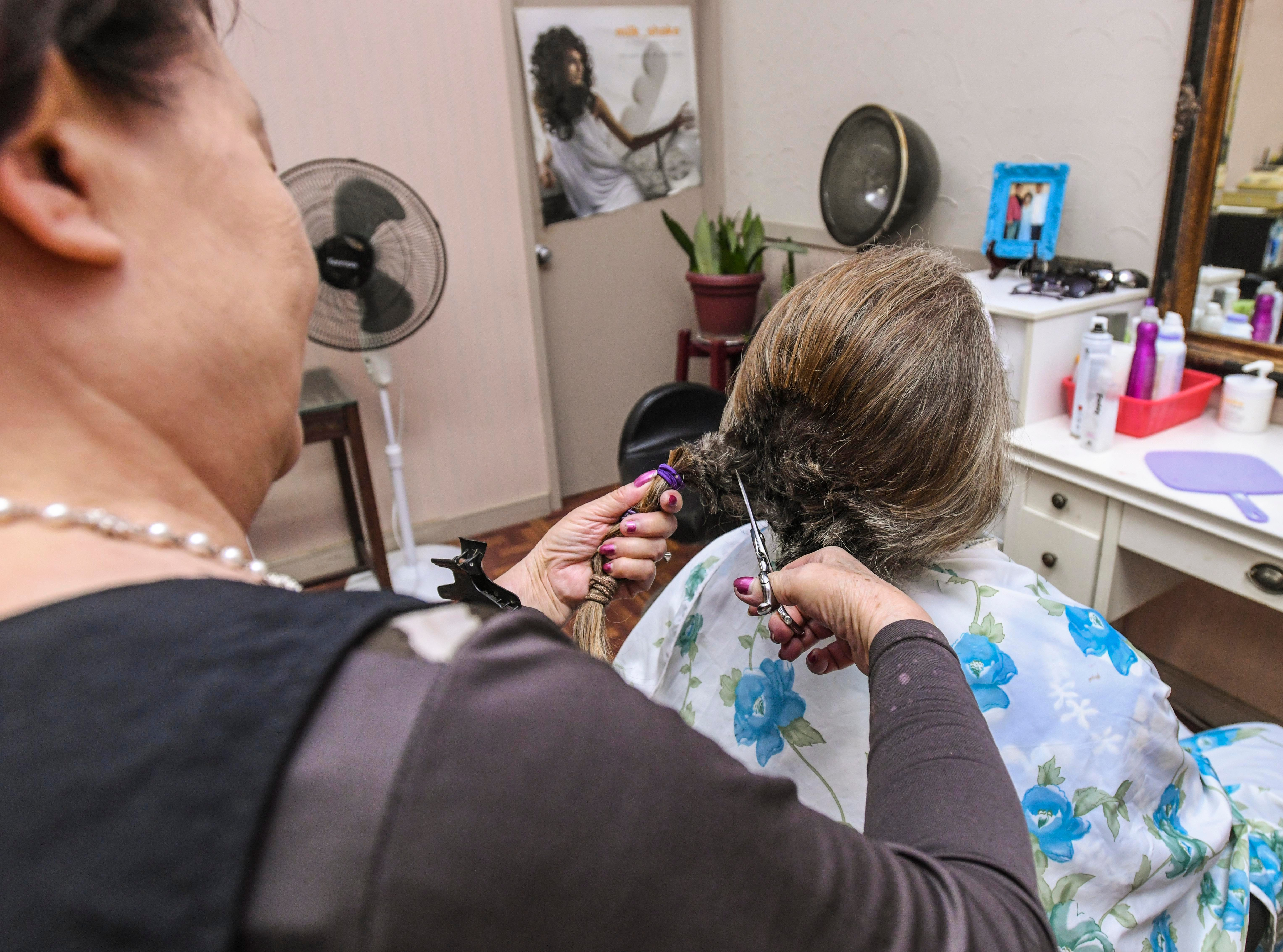 Suzzi Jung, standing, cuts a long length of hair from Shepherd DeBenedictis at the Grace Beauty Shop in Tamuning on Wednesday, Feb. 6, 2019. DeBenedictis, and his daughter, Raylene DeBenedictis, 12, both had their hair cut, with the intention to donate their locks to Wigs for Kids and 360 Hair Inc., respectively, to be fabricated into wigs for people suffering from medical hair loss.