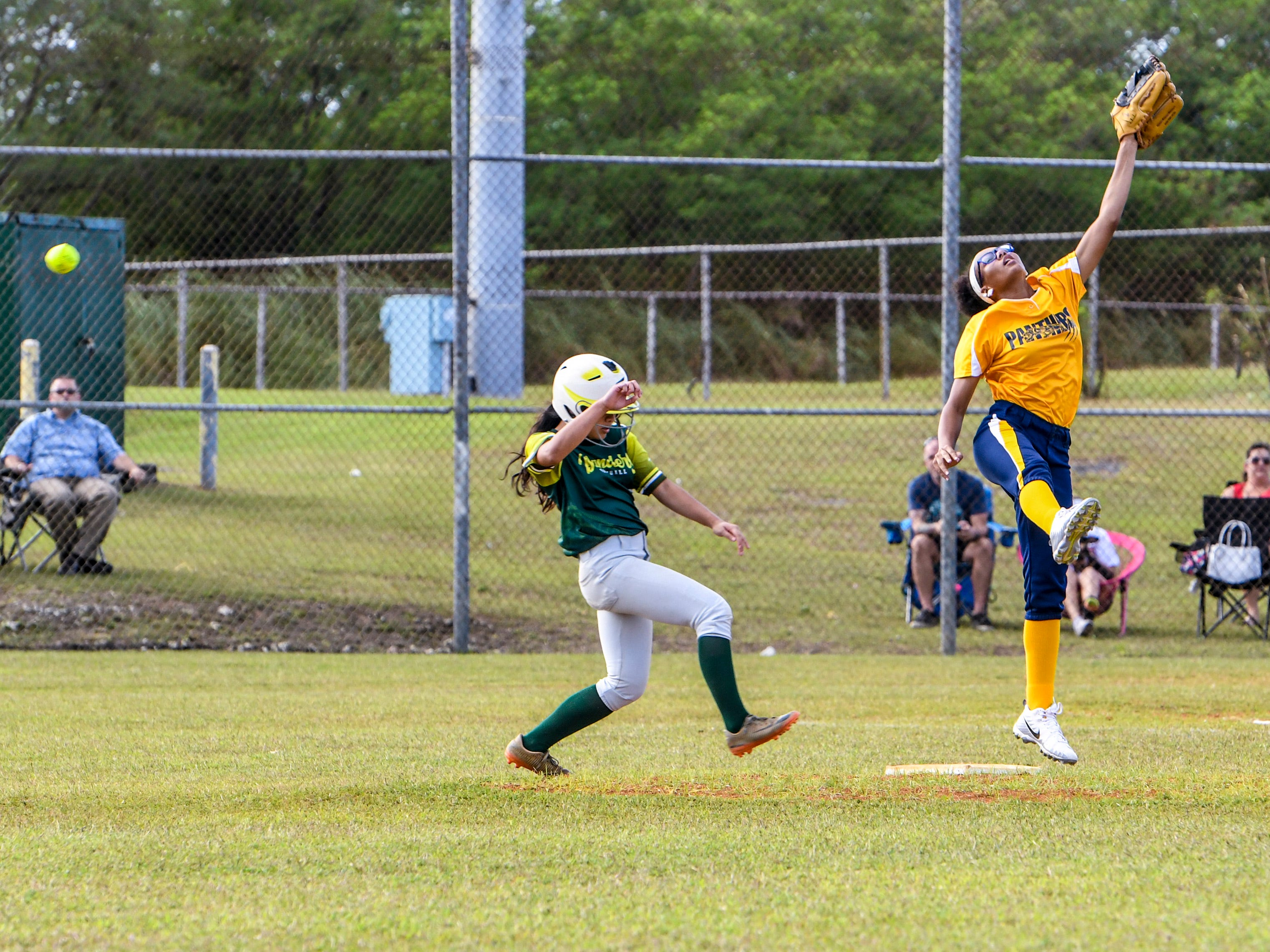 The John F. Kennedy Islanders' Emma Iriarte safely rounds second base on a throwing error during an IIAAG girls softball game with the Guam High Panthers at the JFK High School campus in Tamuning on Thursday, Feb. 7, 2019.