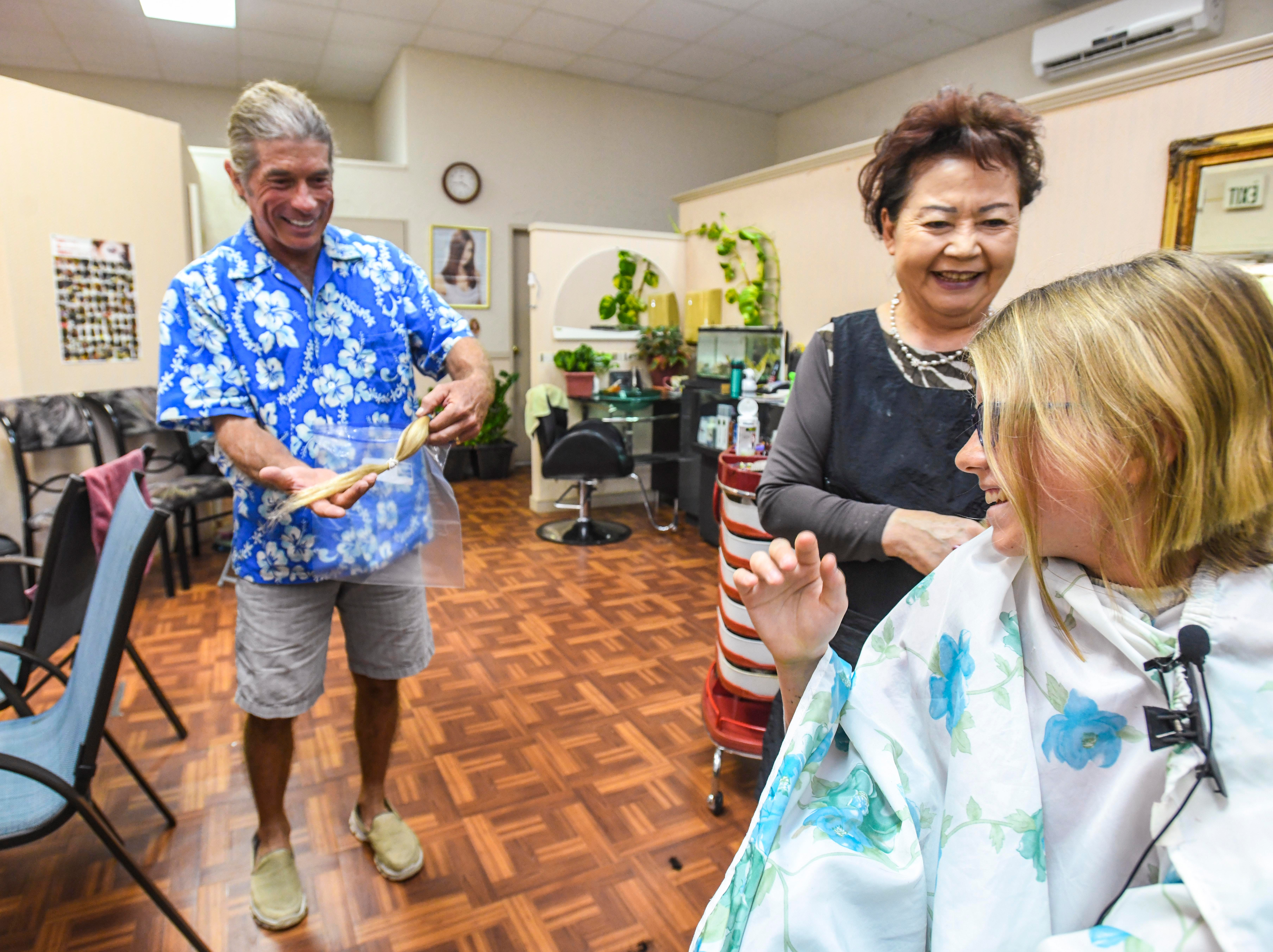 Shepherd DeBenedictis, left, holds a ponytail cut fromthe head of his daughter, Raylene DeBenedictis, 12, at the Grace Beauty Shop in Tamuning on Wednesday, Feb. 6, 2019. The father-daughter duo plan to donate separate locks of their hair to 360 Hair Inc. and Wigs for Kids, respectively, to be fabricated into wigs for people suffering from medical hair loss.