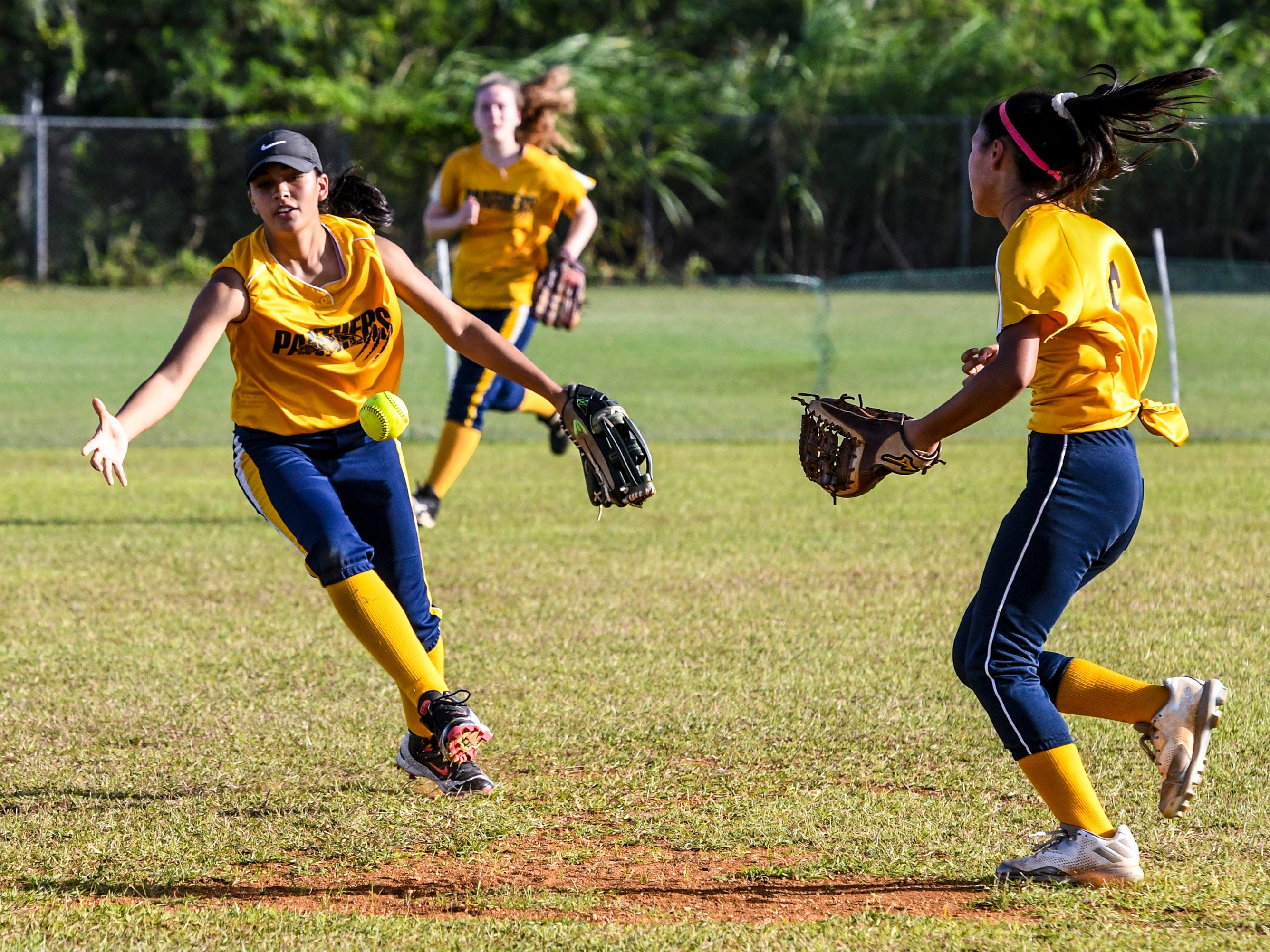 Guam High Panthers infielders scramble for the ball during their matchup with the John F. Kennedy Islanders at the JFK High School campus in Tamuning on Thursday, Feb. 7, 2019.