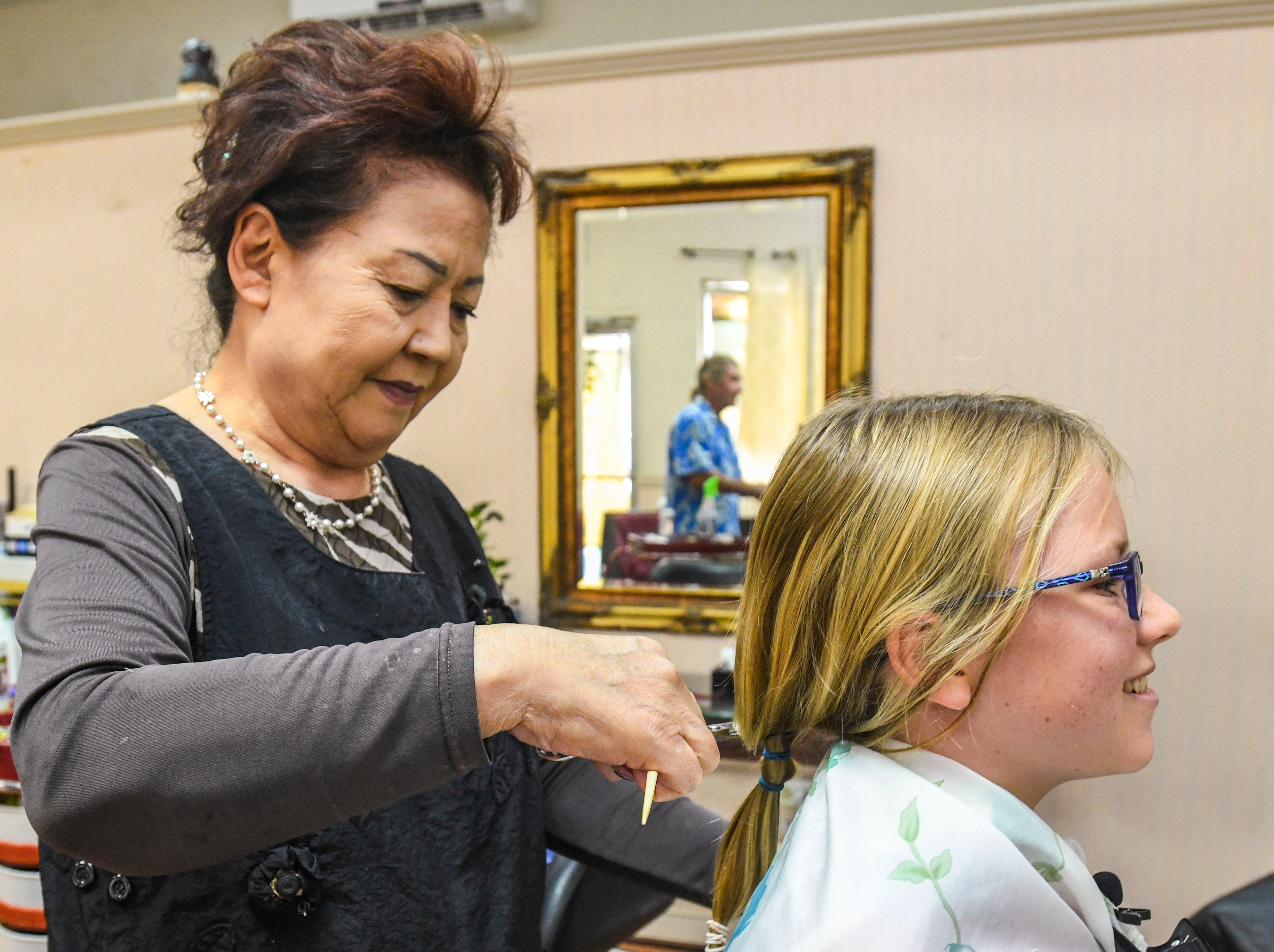 Suzzi Jung, standing, cuts a long tied length of hair from Raylene DeBenedictis, 12, at the Grace Beauty Shop in Tamuning on Wednesday, Feb. 6, 2019. DeBenedictis, and her father Shepherd both had their long hair cut, with the intention to donate their locks to Wigs for Kids and 360 Hair Inc., respectively, to be fabricated into wigs for people suffering from medical hair loss.