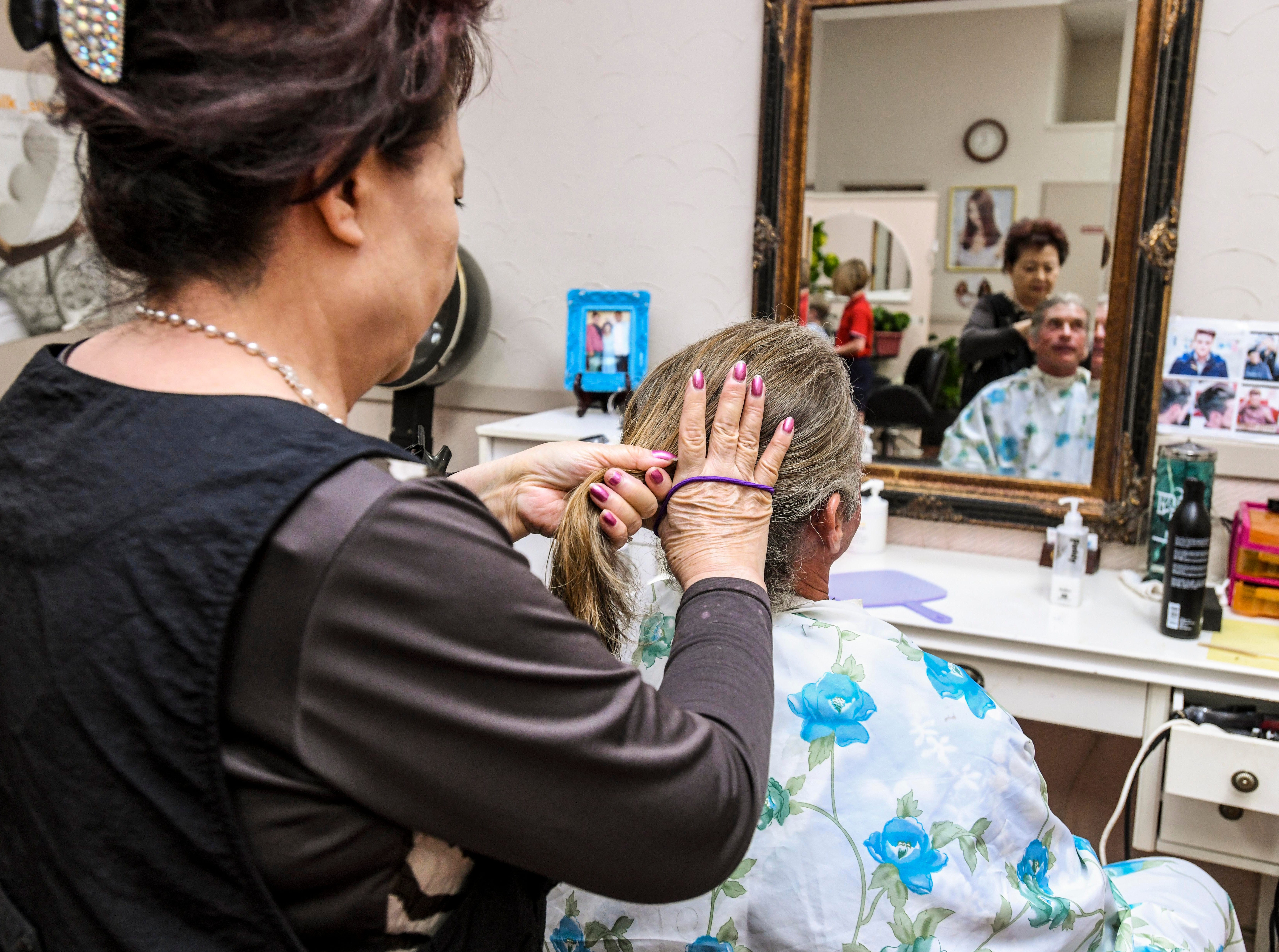 Suzzi Jung, standing, ties a long length of hair from Shepherd DeBenedictis in preparation to cutting off the ponytail at the Grace Beauty Shop in Tamuning on Wednesday, Feb. 6, 2019. DeBenedictis, and his daughter, Raylene DeBenedictis, 12, both had their hair cut, with the intention to donate their locks to Wigs for Kids and 360 Hair Inc., respectively, to be fabricated into wigs for people suffering from medical hair loss.