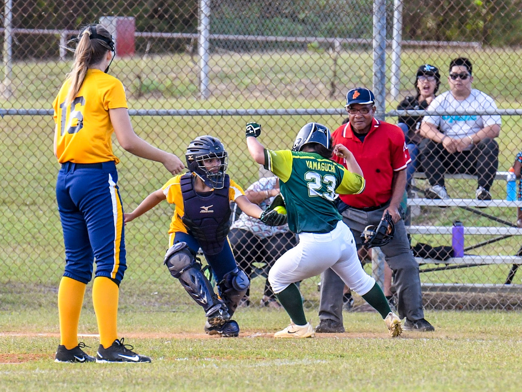 The John F. Kennedy Islanders' Kiyoni Yamaguchi (23) attempts to dodge a tag waiting for her at home plate during an IIAAG girls softball game against the Guam High Panthers at the JFK High School campus in Tamuning on Thursday, Feb. 7, 2019.