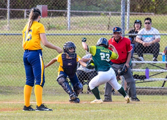 JFK's Kiyoni Yamaguchi (23) attempts to dodge a tag waiting for her at home plate during an IIAAG girls softball game against the Guam High Panthers in this Feb. 7 file photo.
