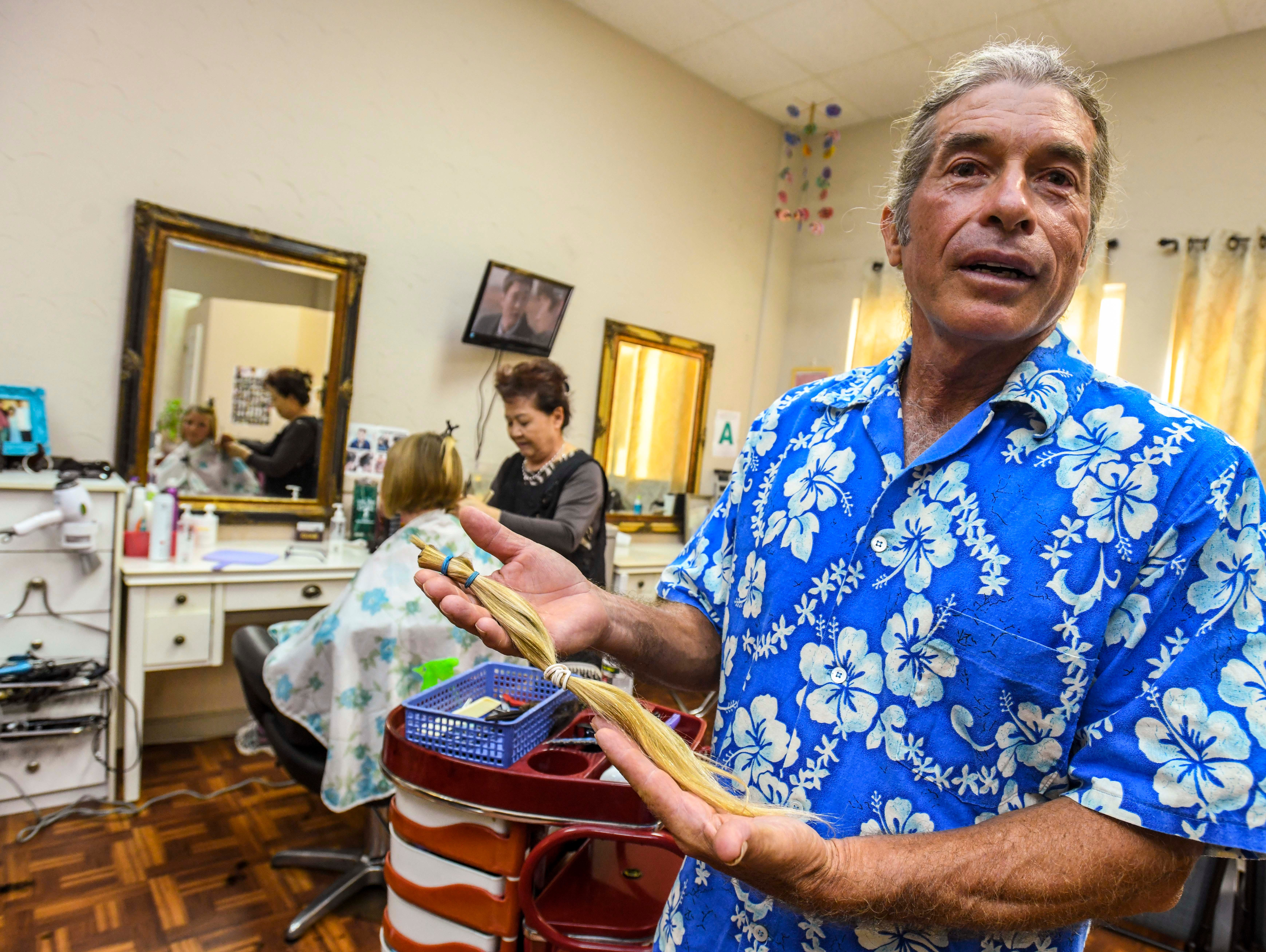 Shepherd DeBenedictis, front, holds a ponytail cut fromthe head of his daughter, Raylene DeBenedictis, 12, at the Grace Beauty Shop in Tamuning on Wednesday, Feb. 6, 2019. The father-daughter duo plan to donate separate locks of their hair to 360 Hair Inc. and Wigs for Kids, respectively, to be fabricated into wigs for people suffering from medical hair loss.