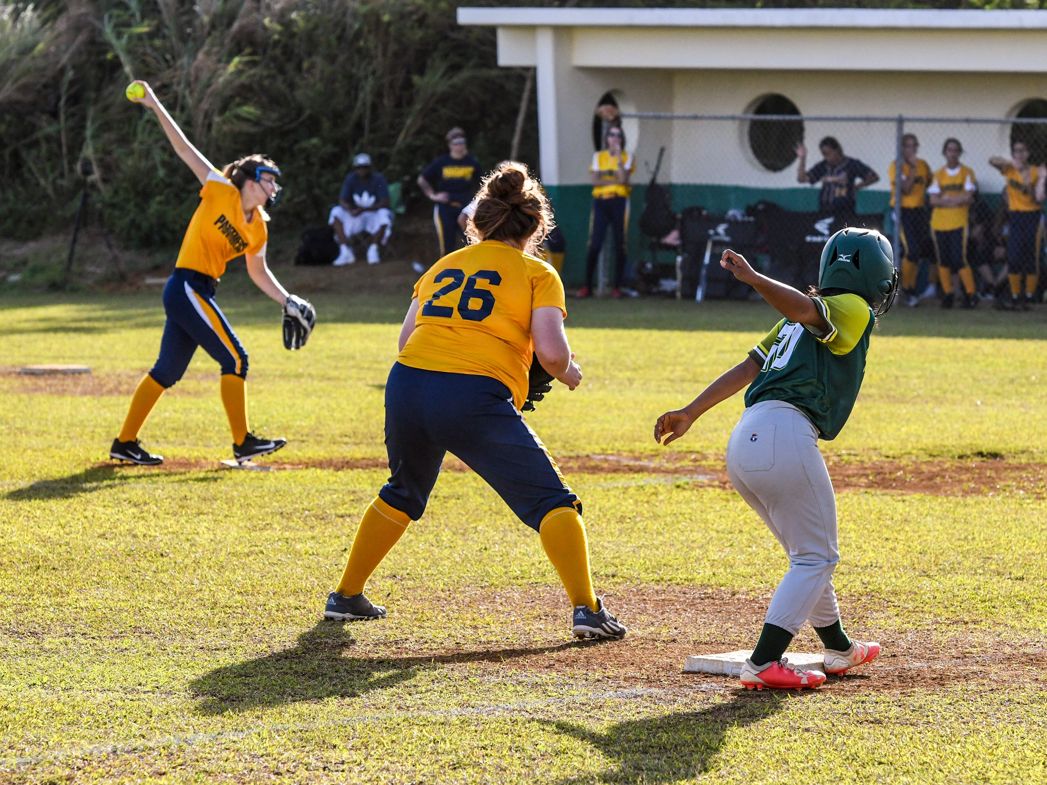The John F. Kennedy Islanders third-base runner Randi Aflleje (20) mimics Guam High Panthers pitcher, Lexi Blyth, as she attempts to head to home plate to score during their IIAAG girls softball matchup at the JFK High School campus in Tamuning on Thursday, Feb. 7, 2019.