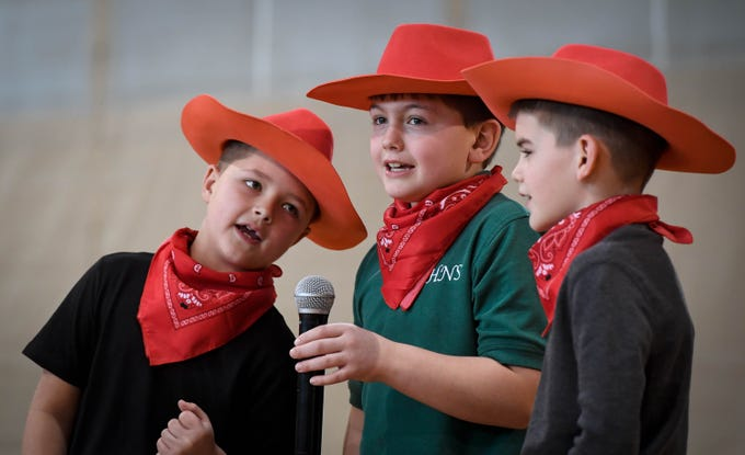 Riding the range, second graders, left to right, Paxden Beck, Owen Smith and Alex Barron sing during the Catholic Schools Week Talent Show at Henderson's Holy Name School Wednesday, February 6, 2019.