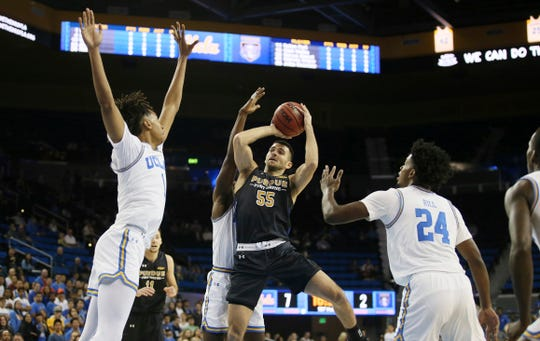 Fort Wayne guard John Konchar, center, attempts a shot between UCLA center Moses Brown, left, guard Prince Ali, rear obstructed, and guard Jalen Hill, right, during the first half of an NCAA college basketball game.