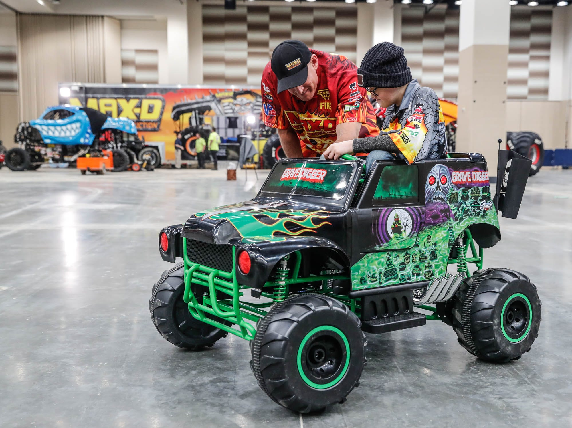 St. Barnabas Catholic School fourth grader, James Egold, who just completed chemo therapy, gets driving instructions from Maximum Destruction monster truck driver Tom Meents, while sitting in a mini Grave Digger Monster Truck, behind the scenes of the Monster Jam at Lucas Oil Stadium on Thursday, Feb. 7, 2019. The visit was thanks to a team up by Monster Jam and Love Your Melon to remodel Egold's room at home while Egold met with Maximum Destruction monster truck driver Tom Meents.