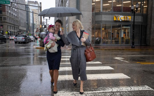 Rachael Denhollander (left), with her baby Elora, and fellow Larry Nassar survivor Sarah Klein walk in a rainstorm to an appearance at U.S. Bankruptcy Court, Birch Bayh Federal Building, Indianapolis, Thursday, Feb. 7, 2019. They are attending the hearing involving USA Gymnastics CFO Scott Shollenbarger, representing the organization that has sought bankruptcy protection in the aftermath of disgraced former doctor Larry NassarÕs arrest and imprisonment.