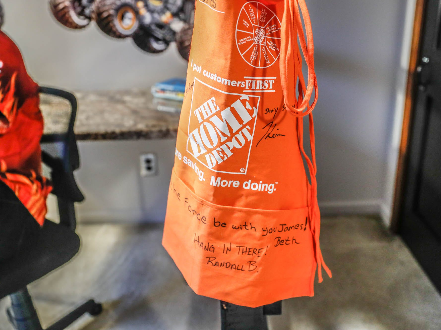 A Home Depot apron signed by a remodeling team hangs in the newly remodeled room of St. Barnabas Catholic School fourth grader, James Egold, who just completed chemo therapy, on Thursday, Feb. 7, 2019. The remodel was thanks to a team up by Monster Jam, Love Your Melon, and Home Depot.