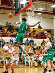 Valparaiso's Brandon Newman (1) leaps to block a shot and ends up in the stands during a game against Zionsville, Dec. 22, 2018.