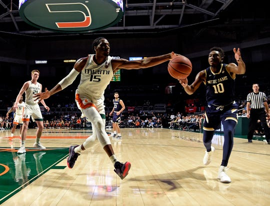 Feb 6, 2019; Coral Gables, FL, USA; Miami Hurricanes center Ebuka Izundu (15) and Notre Dame Fighting Irish guard TJ Gibbs (10) both reach for a loose ball during the first half at Watsco Center.