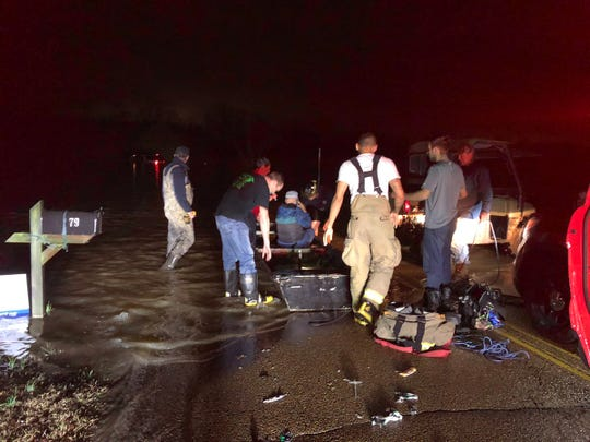 A Madison County Fire Department crew uses a borrowed boat to rescue a person from a water-logged vehicle on Mason Road near Three Way on Wednesday night.