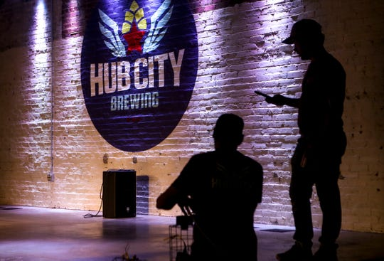 Pat Keith, a Delta Electric electrical technician, left, and Lewis Silvers with Hub City test out the lights to be used on the stage at Hub City Brewing in Jackson.