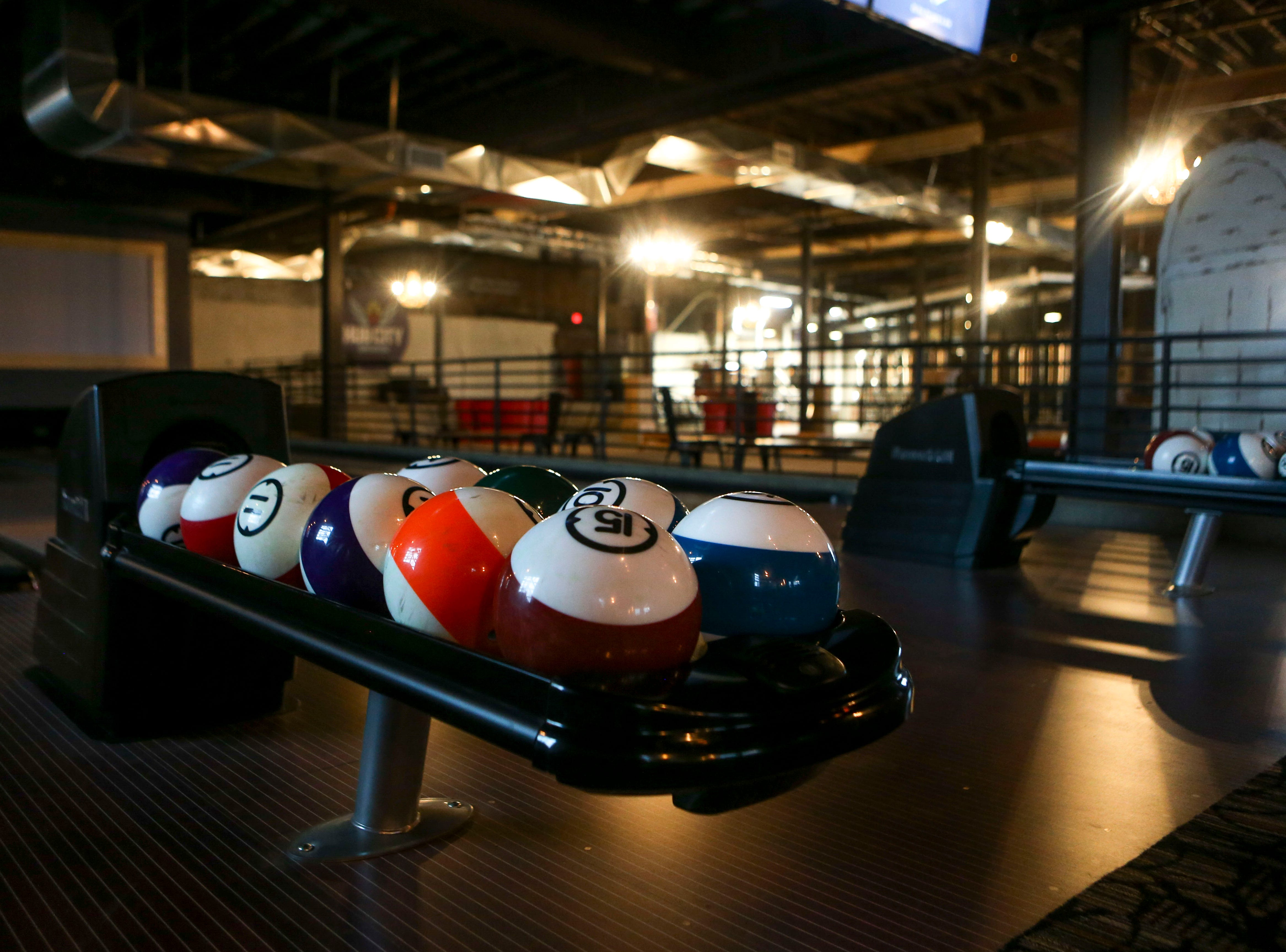 Bowling balls can be seen in their storage spots at the lanes at Hub City Brewing in Jackson, Tenn., on Wednesday, Feb. 6, 2019.