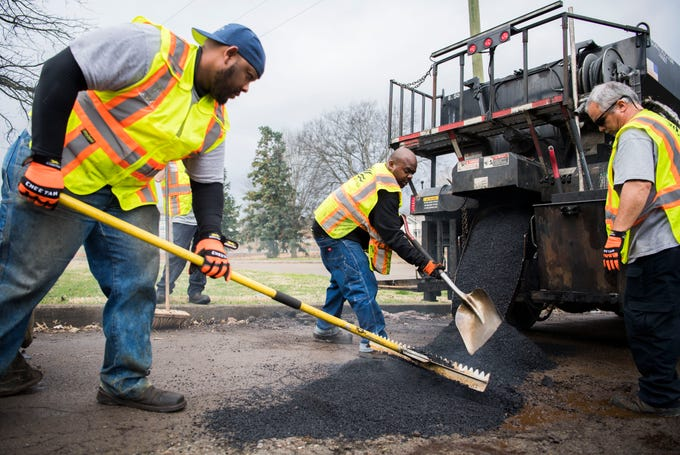 From left, Knoxville city employees Frankie Robinson, Anthony Johnson and Matt Roth fill potholes on Sanders Lane in East Knoxville, Thursday, Feb. 7, 2018