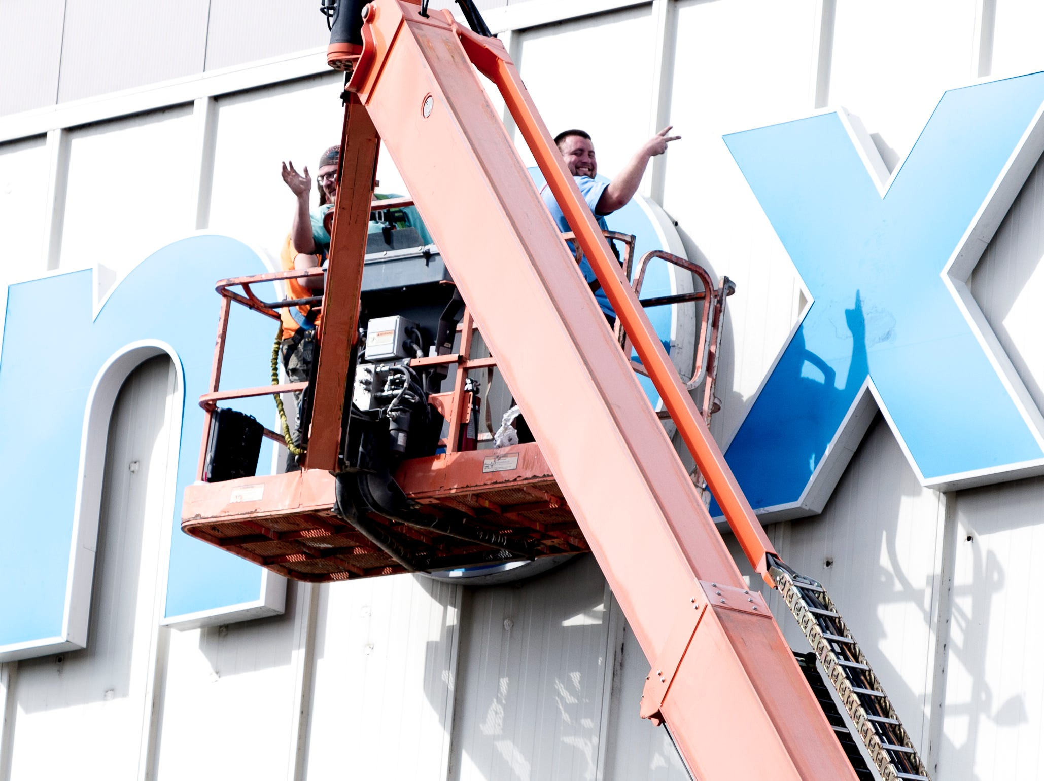 """Workers from Sycamore Sign Service pose for the camera while installing the """"knox news."""" sign on the front of the Knoxville News Sentinel building on 2332 News Sentinel Dr. in Knoxville, Tennessee on Thursday, February 7, 2019."""