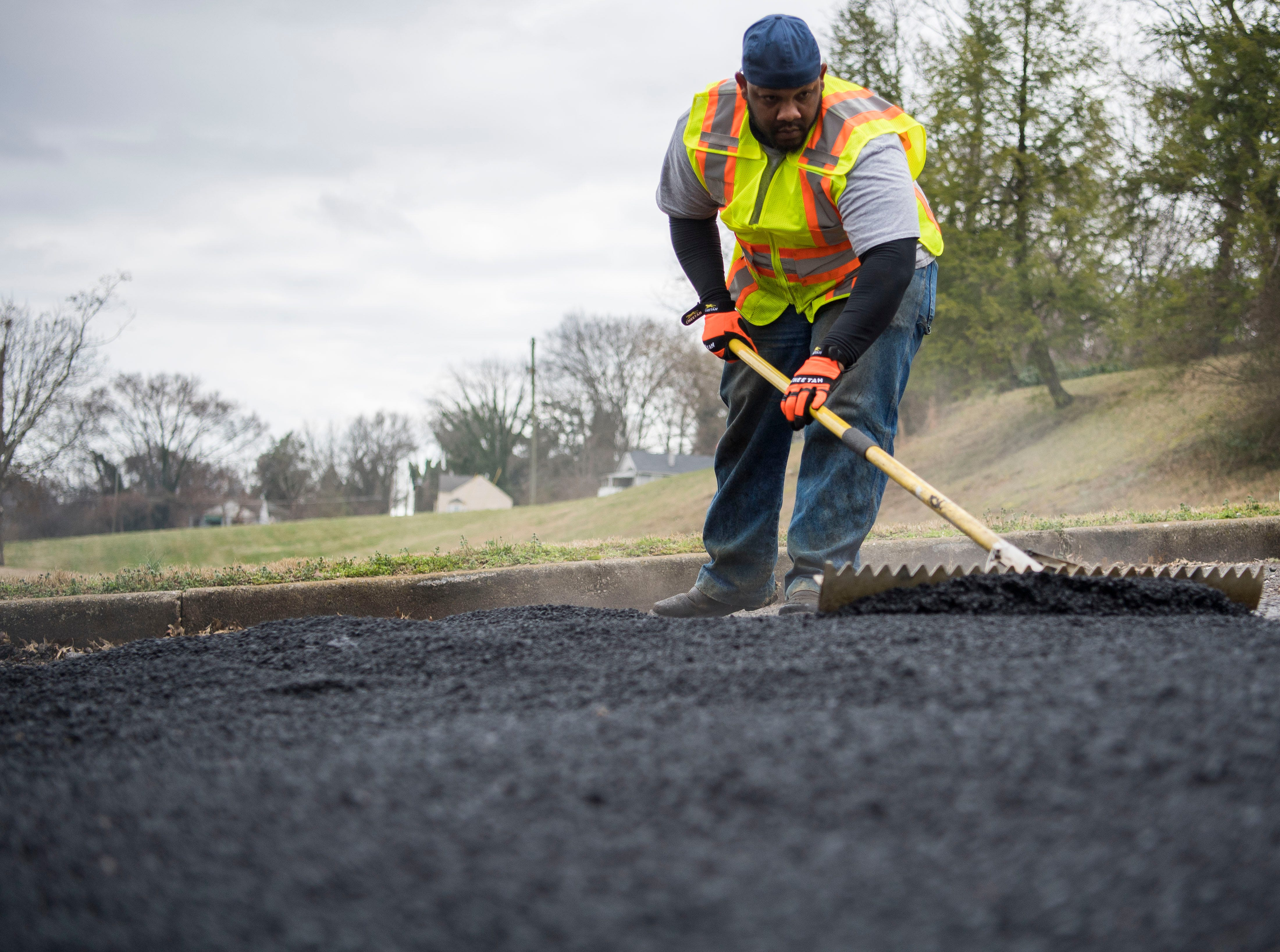 City of Knoxville employee Frankie Robinson levels asphalt as potholes are filled by a City of Knoxville crew on Sanders Lane in East Knoxville, Thursday, Feb. 7, 2018