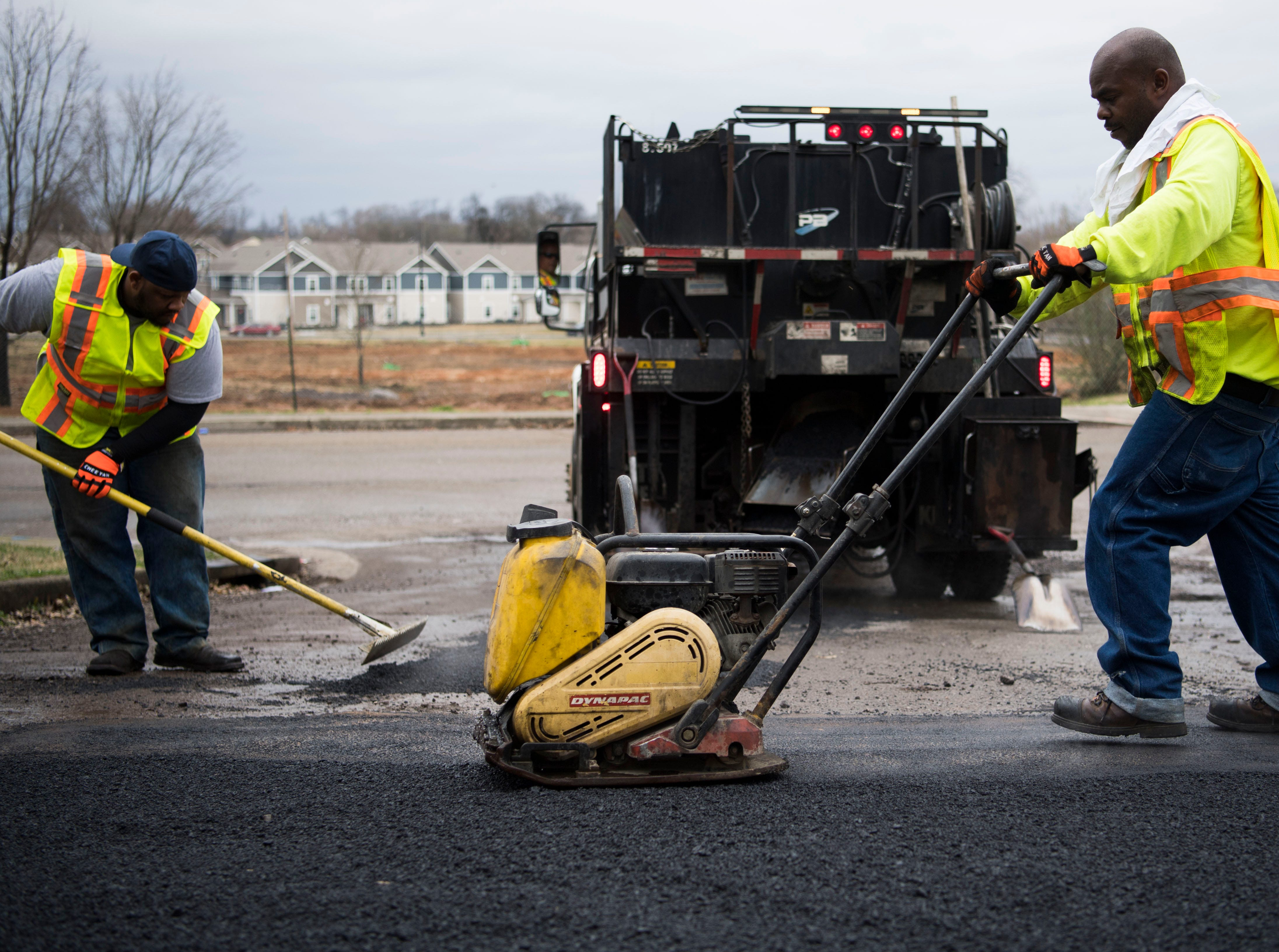 At right Anthony Johnson tamps asphalt as potholes are filled by a City of Knoxville crew on Sanders Lane in East Knoxville, Thursday, Feb. 7, 2018