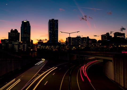 Cars travel on James White Parkway as the sun sets behind the downtown Knoxville skyline on Tuesday, January 8, 2019.
