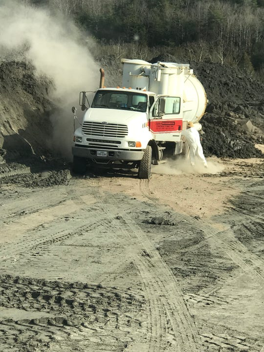 A worker who provided this photo to the Knoxville News Sentinel says it shows coal ash dust swirling around a vehicle and worker Feb. 5 at the TVA Bull Run Fossil Plant in Anderson County, Tennessee. Some contract workers, like this one, wear protective respiratory and body-covering gear, but other contracted companies don't provide the same protective gear, some workers said.