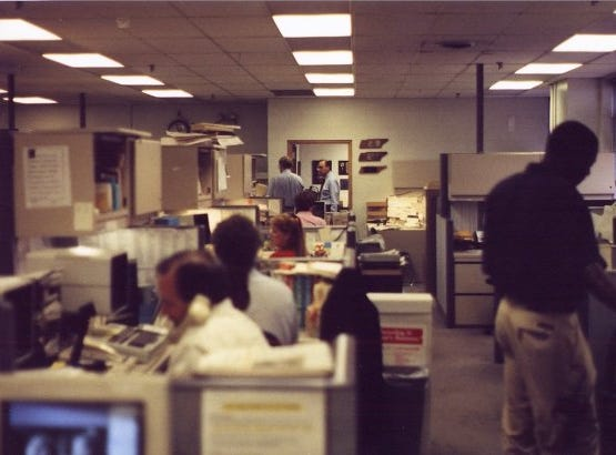 The Knoxville News Sentinel newsroom at 208 W. Church Ave., Knoxville, Tenn., 1994. On the phone is Bob Norris. Sitting behind him are Tom Chester, Donna Colburn and Jan Avent. Standing at right is photographer Byron Small. At the rear, standing with his back to the camera, is Bobby Wilson talking to editor Harry Moskos.