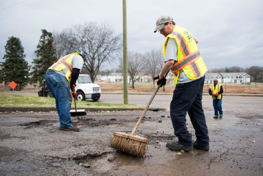 At center City of Knoxville employee Chris Orlandi cleans potholes which are about to be filled by a City of Knoxville crew on Sanders Lane in East Knoxville, Thursday, Feb. 7, 2018