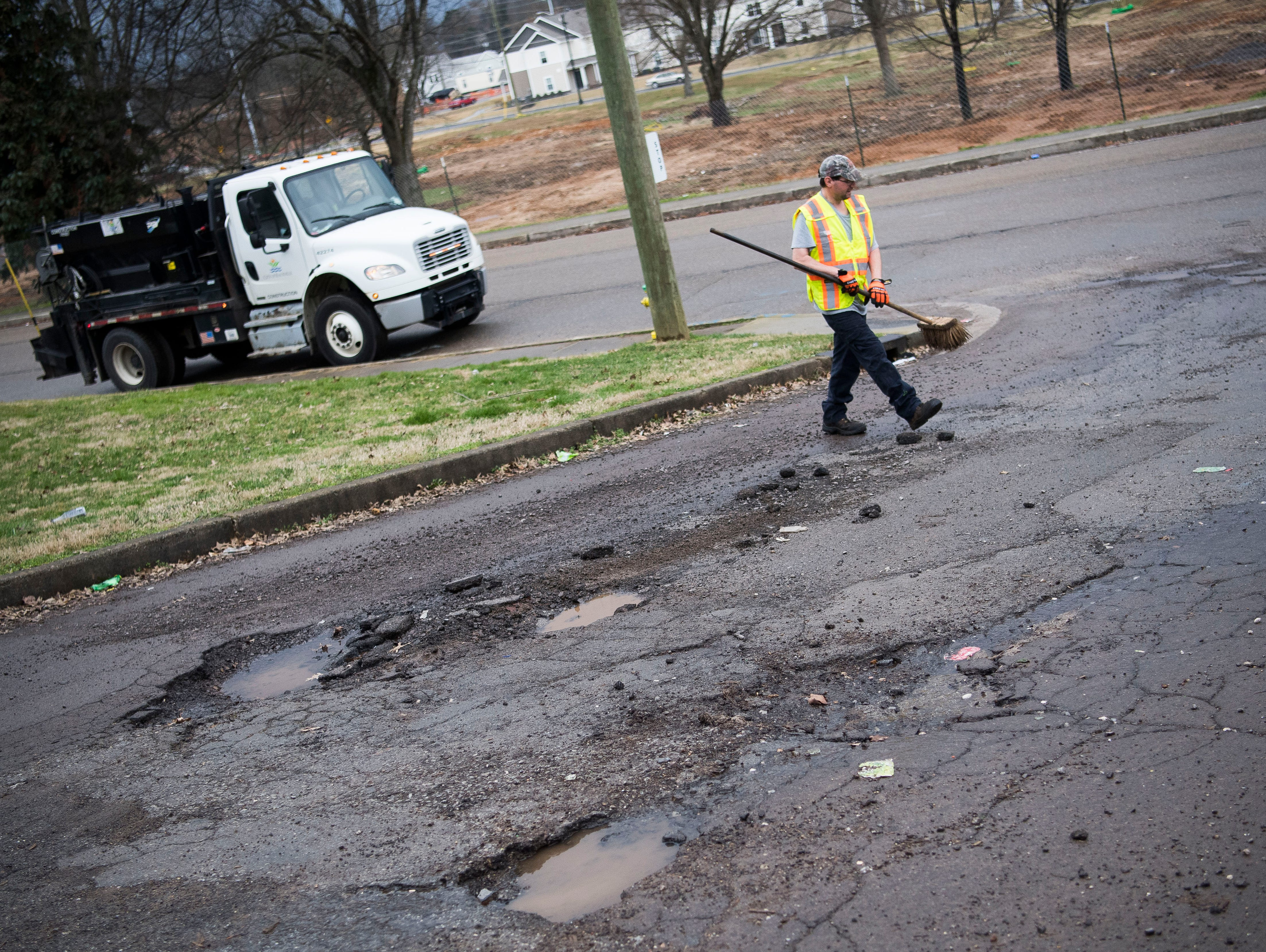 City of Knoxville employee Chris Orlandi walks towards potholes which are about to be filled by a City of Knoxville crew on Sanders Lane in East Knoxville, Thursday, Feb. 7, 2018