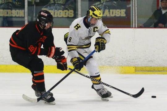 Hartland's Joey Larson (9) and Brighton's AJ Benit (18) battle for the puck during the Eagles' 4-0 victory on Wednesday, Feb. 6, 2019.