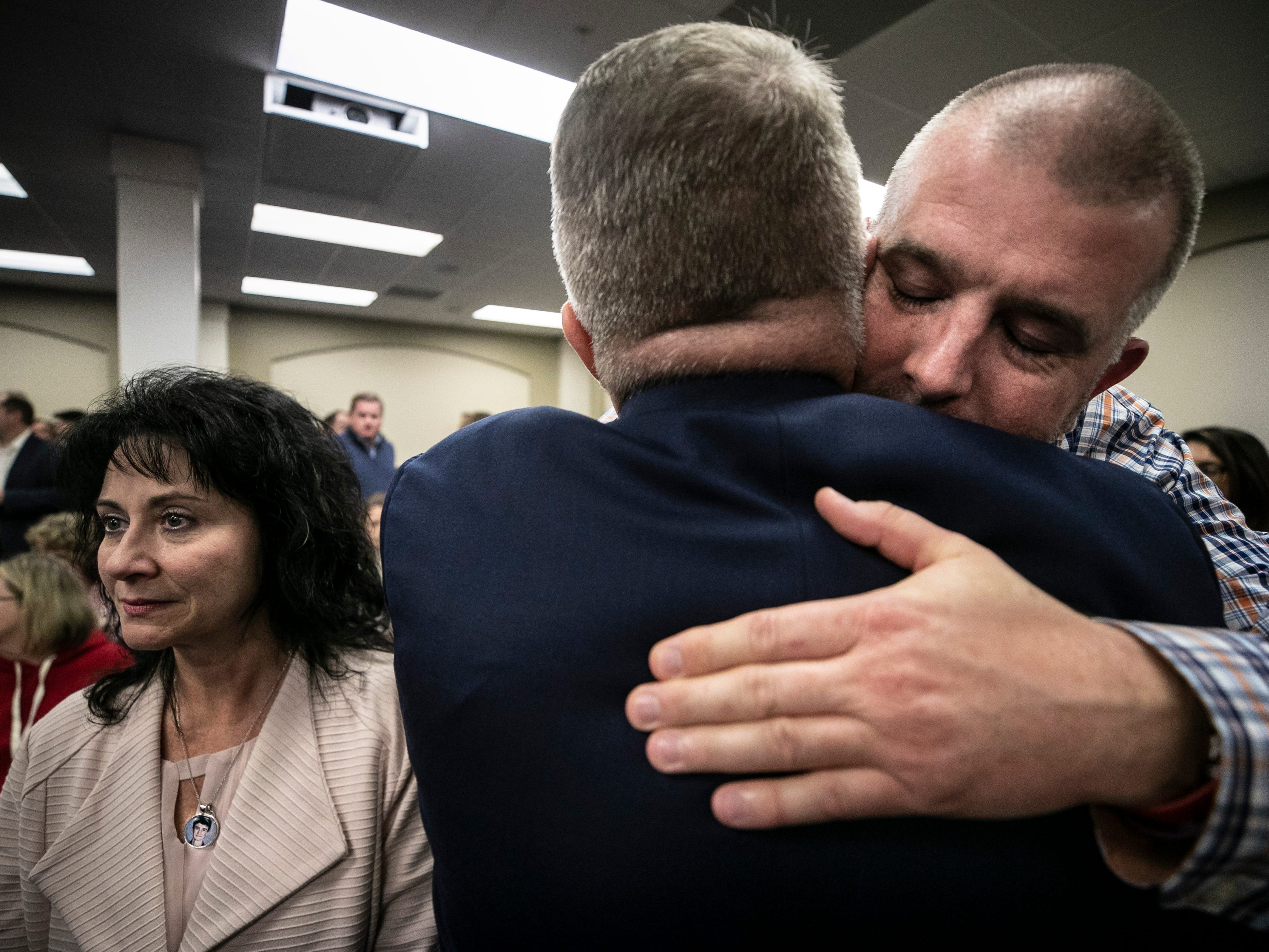 Jasen Holt hugs Kentucky Senator Danny Carroll after a hearing Thursday at the State Capitol. Holt's daughter, 15-year-old Bailey Holt, was one of two teenagers killed in the Marshall County High School shooting in 2018. At left is Theresa Cope, who wore a pendant with a picture of her son Preston, who also died in the shooting.
