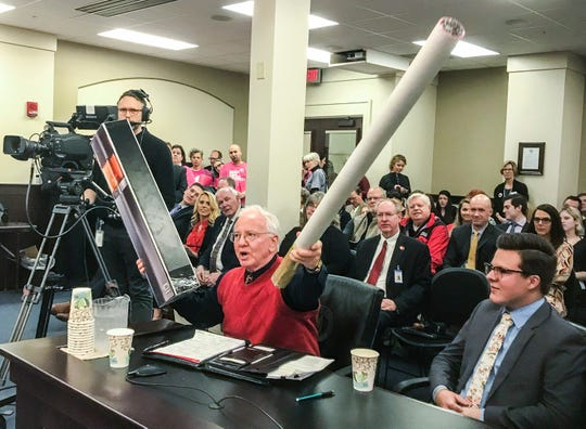 Dr. Pat Withrow holds up a giant cigarette during a hearing last month at the state capitol about banning tobacco use in public schools. Withrow is a retired cardiologist.