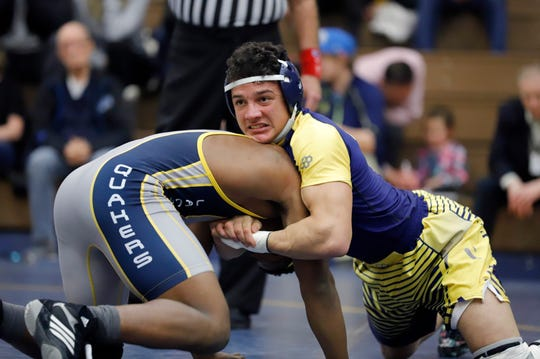 DeWitt's Quenten Hall, right, grapples with Lansing Eastern's Devin Toles, Wednesday, Feb. 6, 2019, in Lansing, Mich. DeWitt won 74-6.