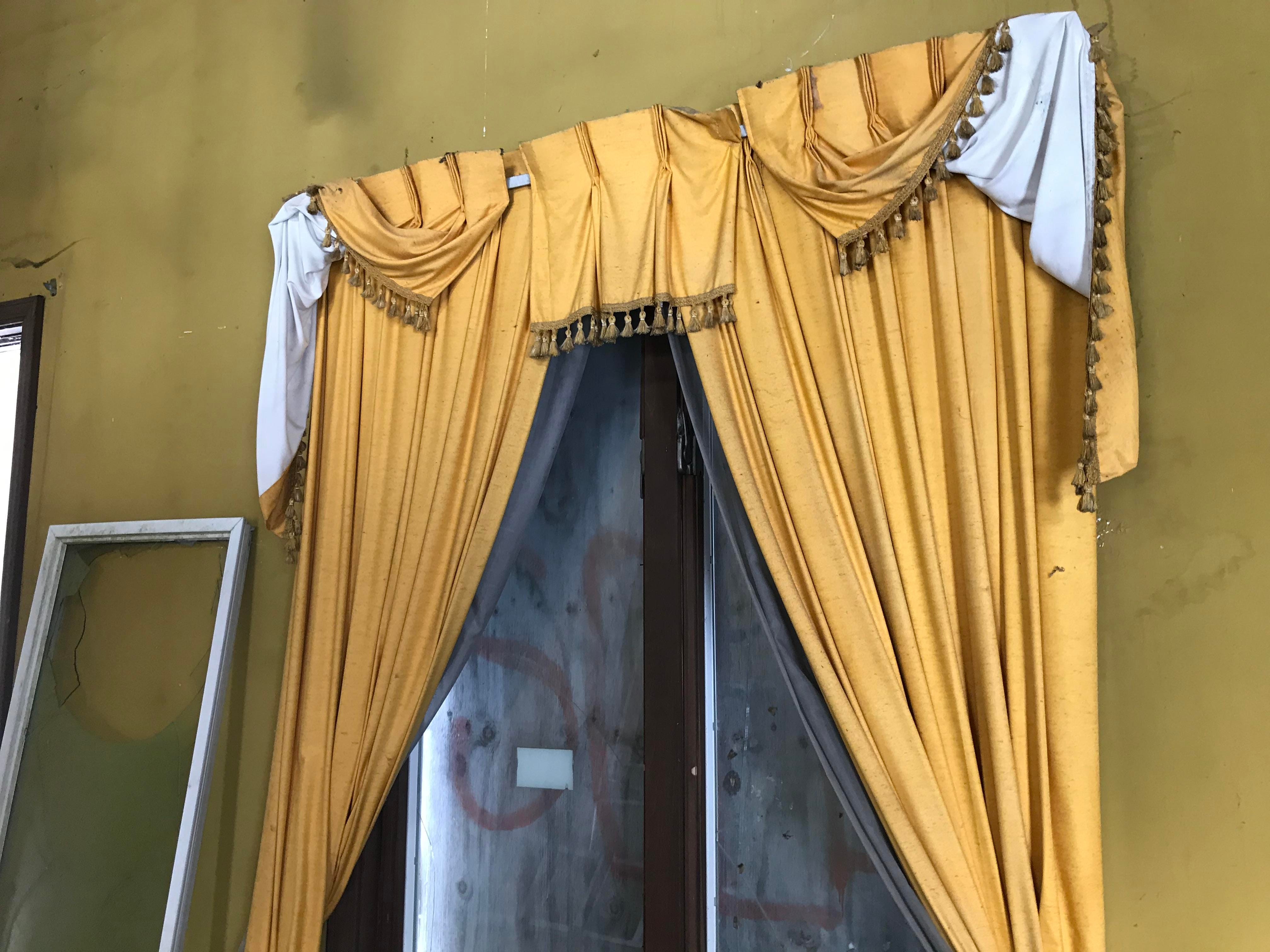 "Drapes on a first-floor window at an abandoned home on Billwood Highway. Often referred to as ""the Addams Family house,"" new owner Matt Jankoviak aims to remodel it, and then open a canoe and kayaking livery at the property."