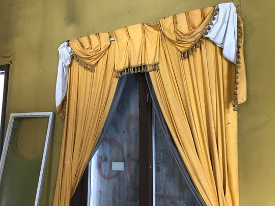 """Drapes on a first-floor window at an abandoned home on Billwood Highway. Often referred to as """"the Addams Family house,"""" new owner Matt Jankoviak aims to remodel it, and then open a canoe and kayaking livery at the property."""
