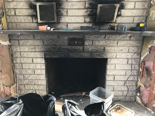 """A fire place in a first-floor room at an abandoned home on Billwood Highway. Often referred to as """"the Addams Family house,"""" new owner Matt Jankoviak aims to remodel it, and then open a canoe and kayaking livery at the property."""